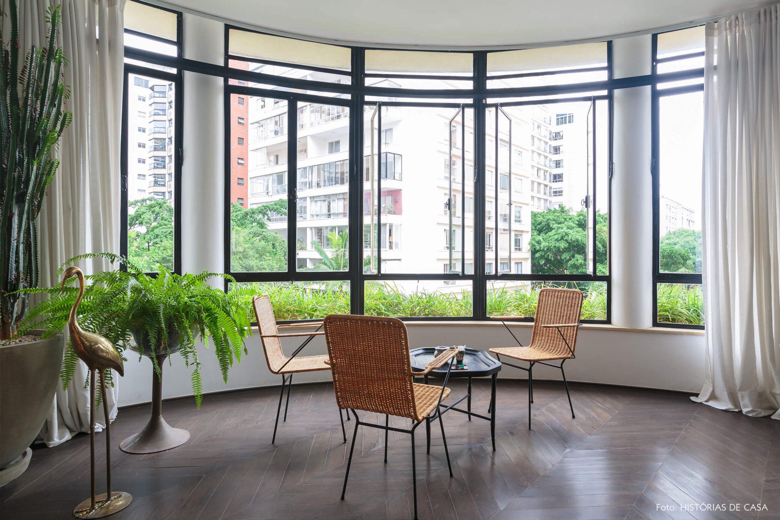 decoração ap sala com janleas grandes, cadeira de palha e plantas