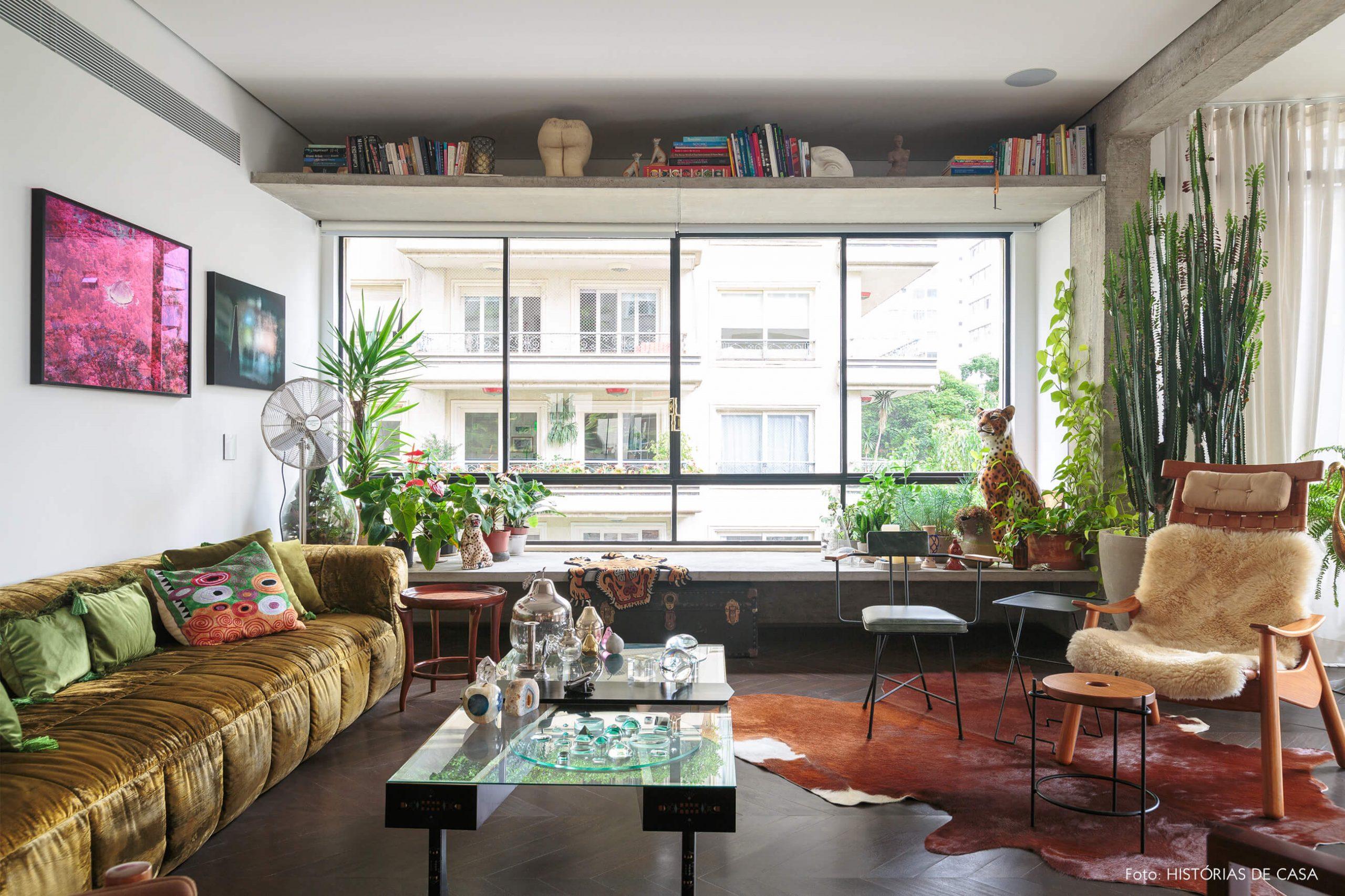 decoração ap sala com sofá de veludo verde e banco de concreto com muitas plantas