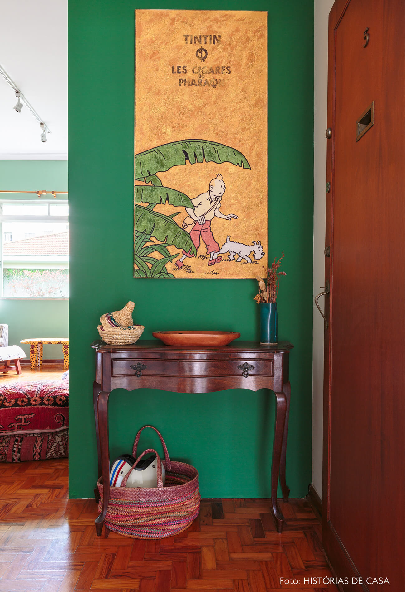 decoração hall com parede verde, cesto e mesa de madeira