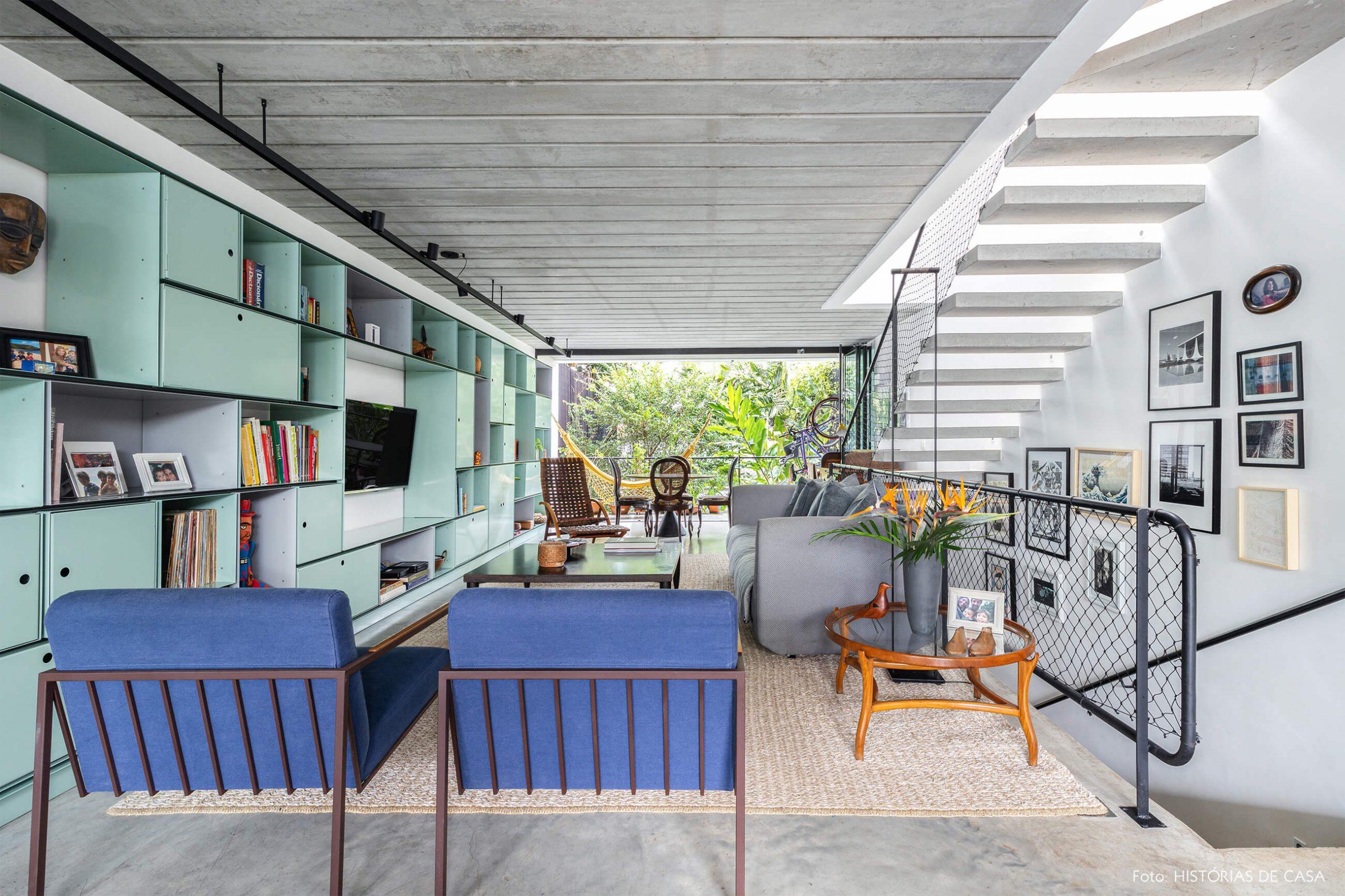 decoração casa sala com poltrona azul estante verde e escada de concreto