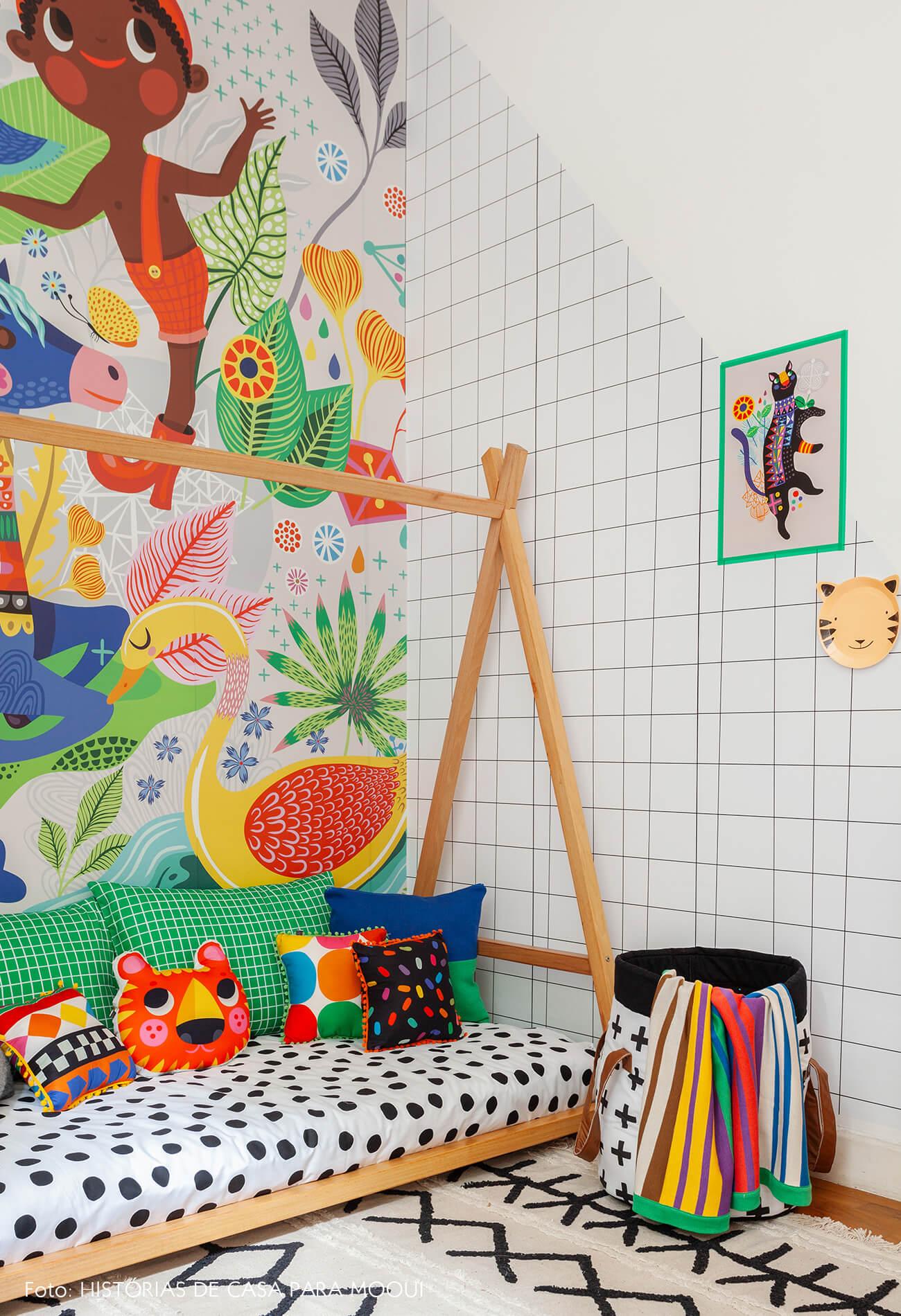 Quarto de criança com papel de parede estampado e cama baixa