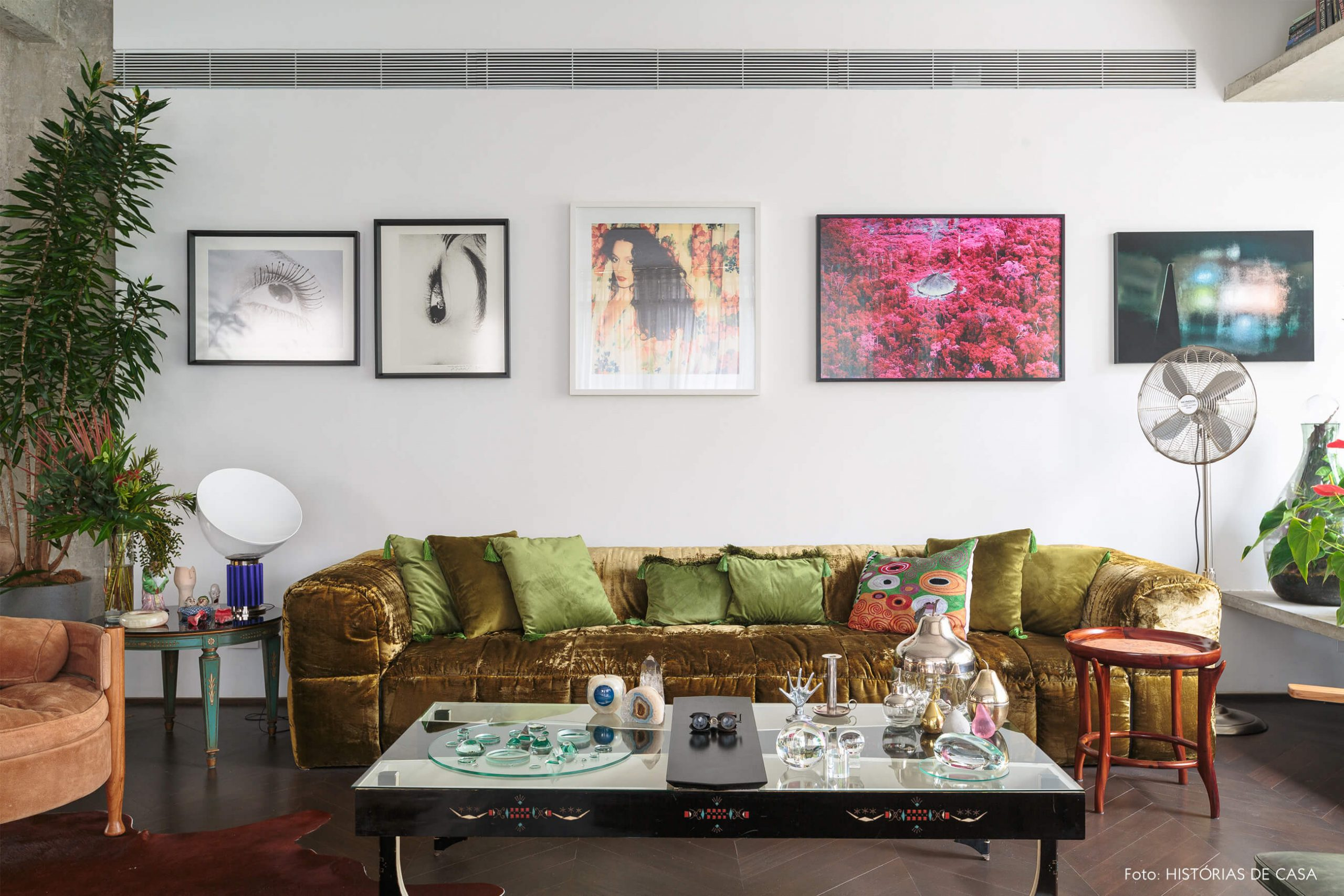 decoração ap sala com sofá de veludo verde, muitos quadros