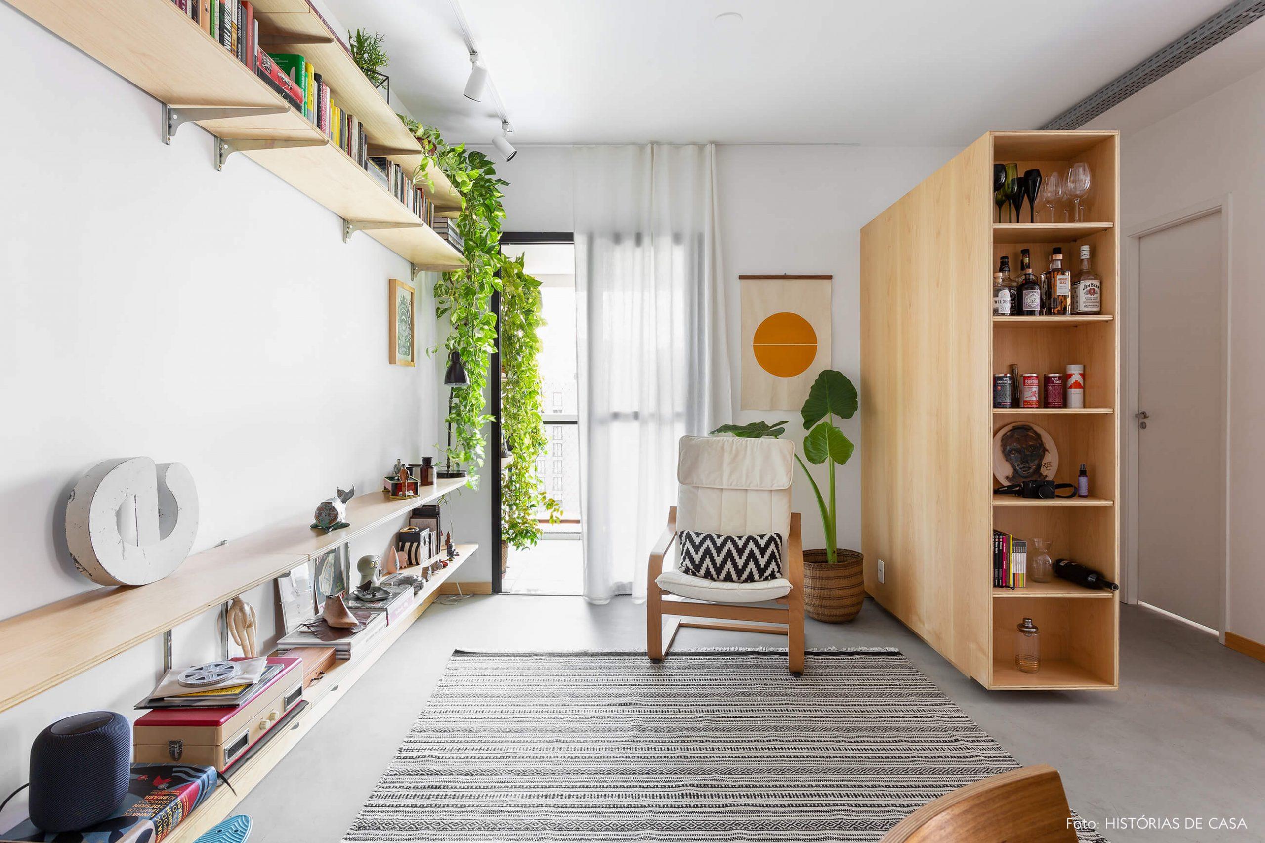 decoração sala com poltrona branca e prateleiras de madeira clara