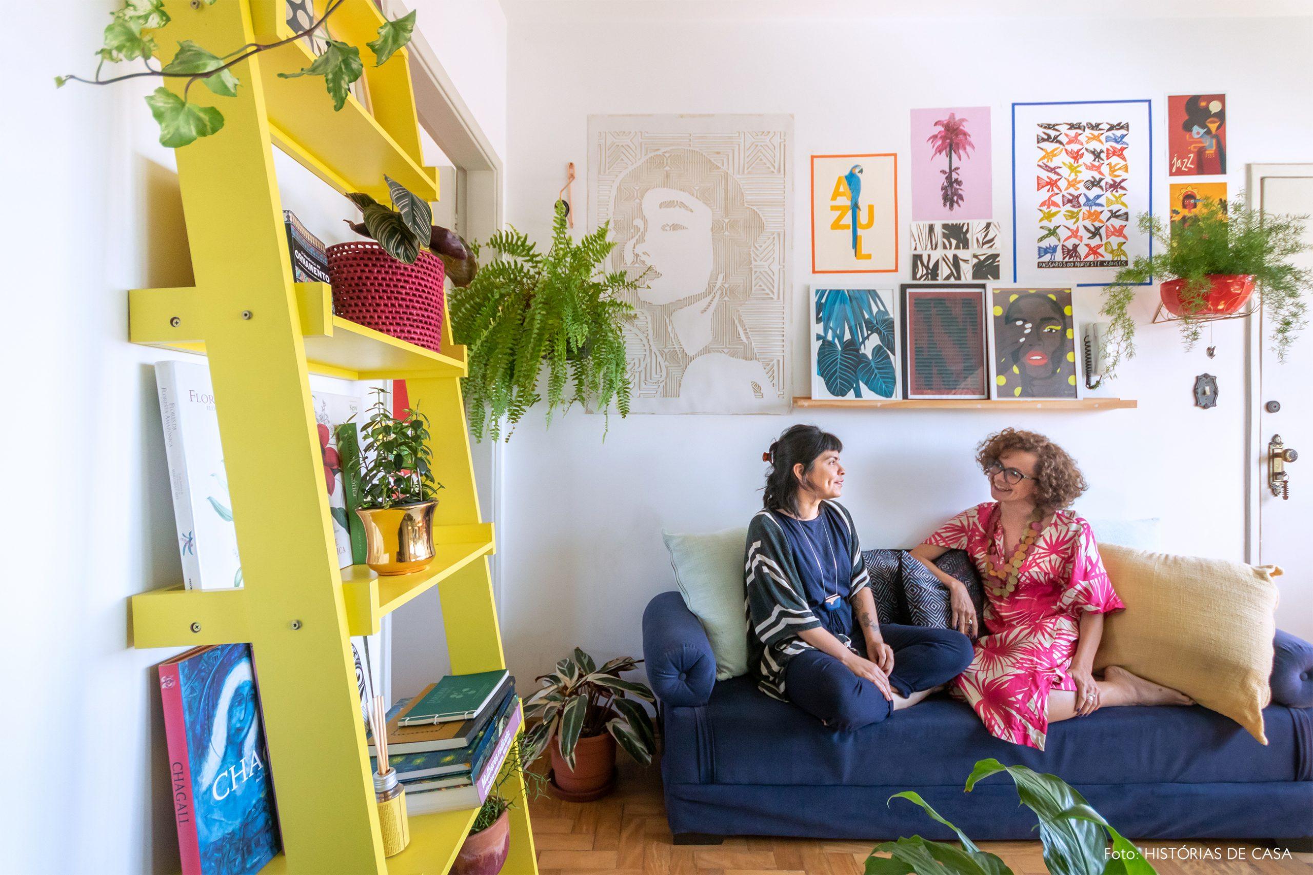 decoração retrato em sala com sofá azul e prateleira amarela