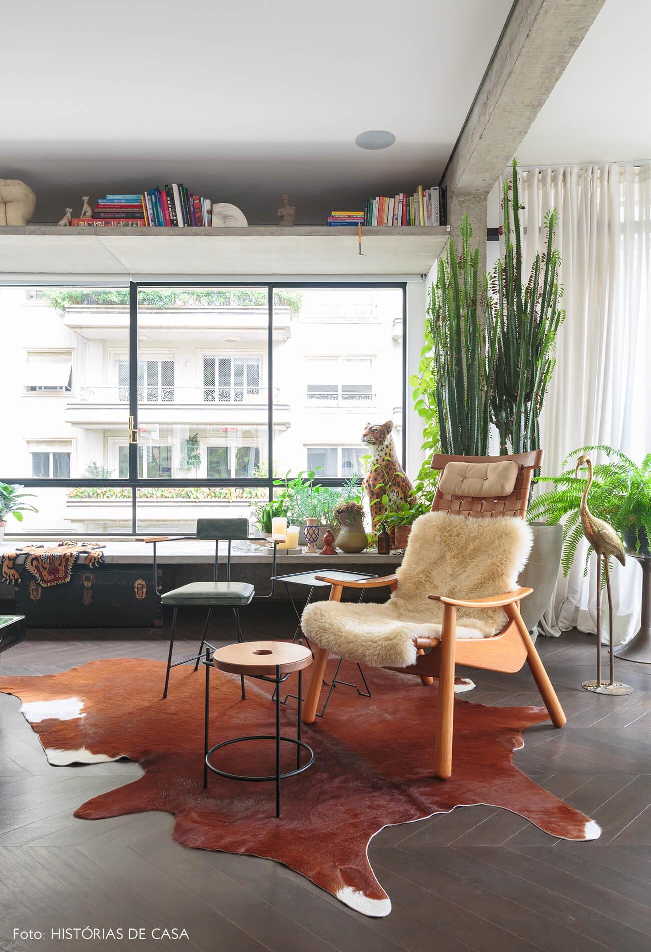 decoração ap sala com poltrona de madeira, plnatas em banco de concreto