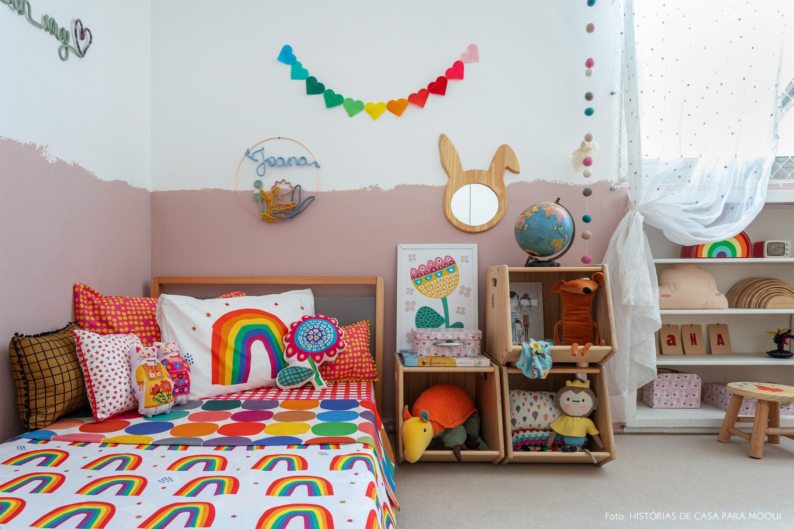 Quarto de criança com roupa de cama de arco-íris