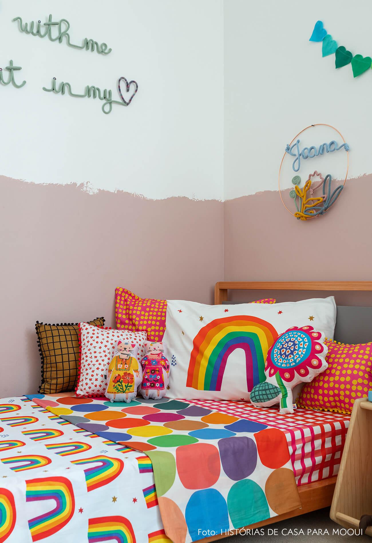 Quarto de menina com parede pintada até metade e roupa de cama de arco-íris