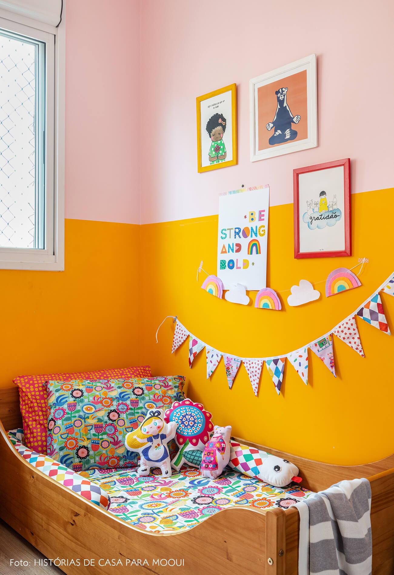 Quarto de criança com meia parede colorida e bandeirinhas