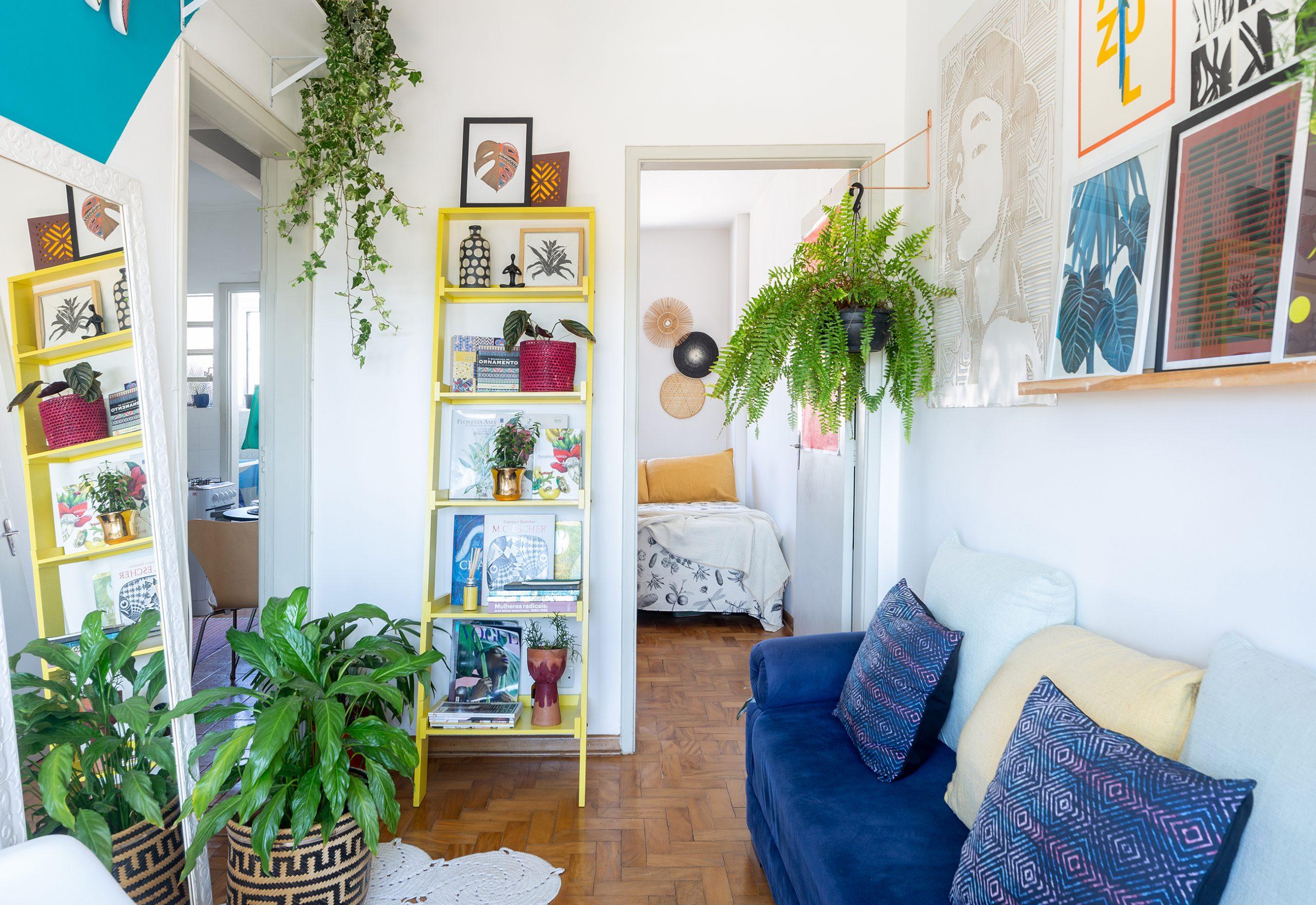 decoração sala com sofá azul, pintura geométrica e cesto