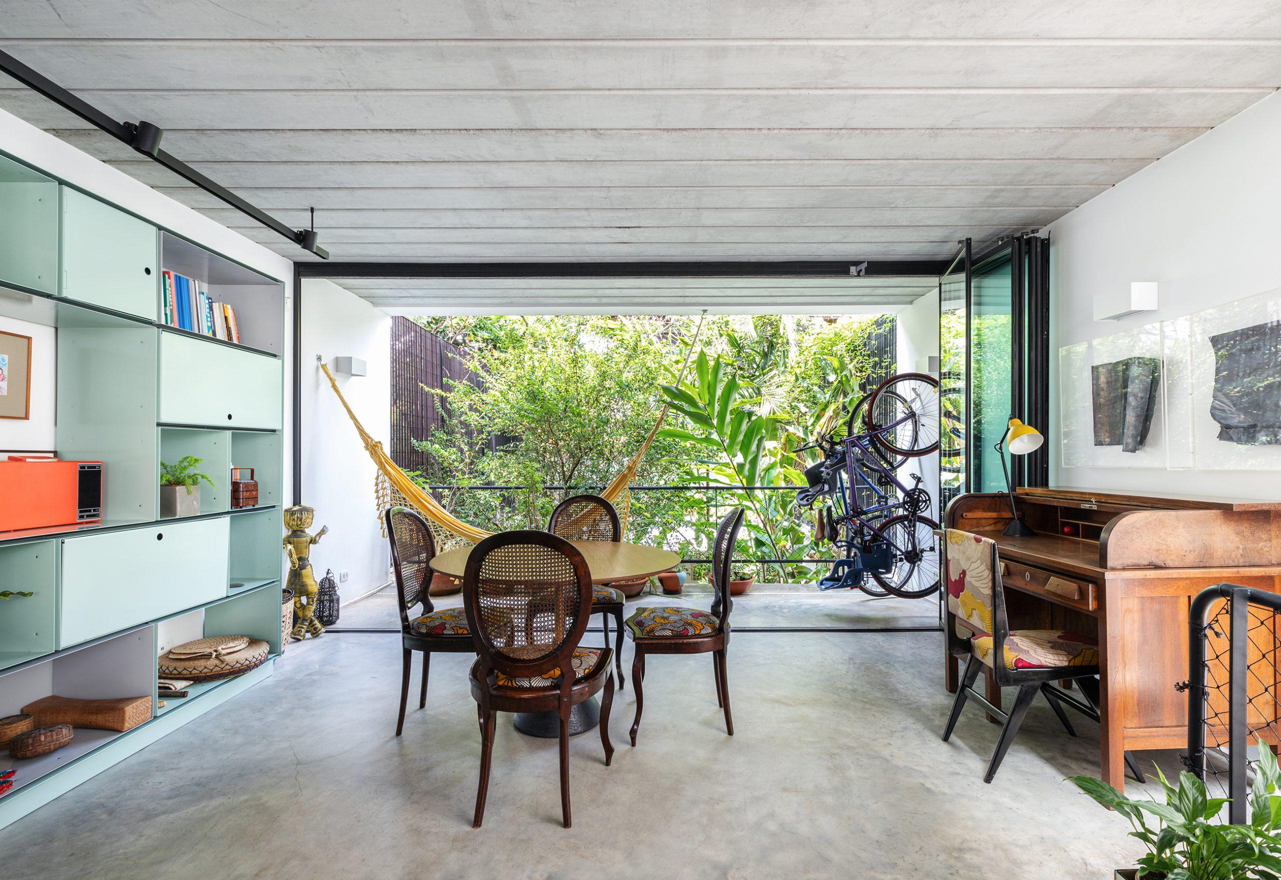 decoração casa sala com estante de metal verde, rede, e mesa de madeira
