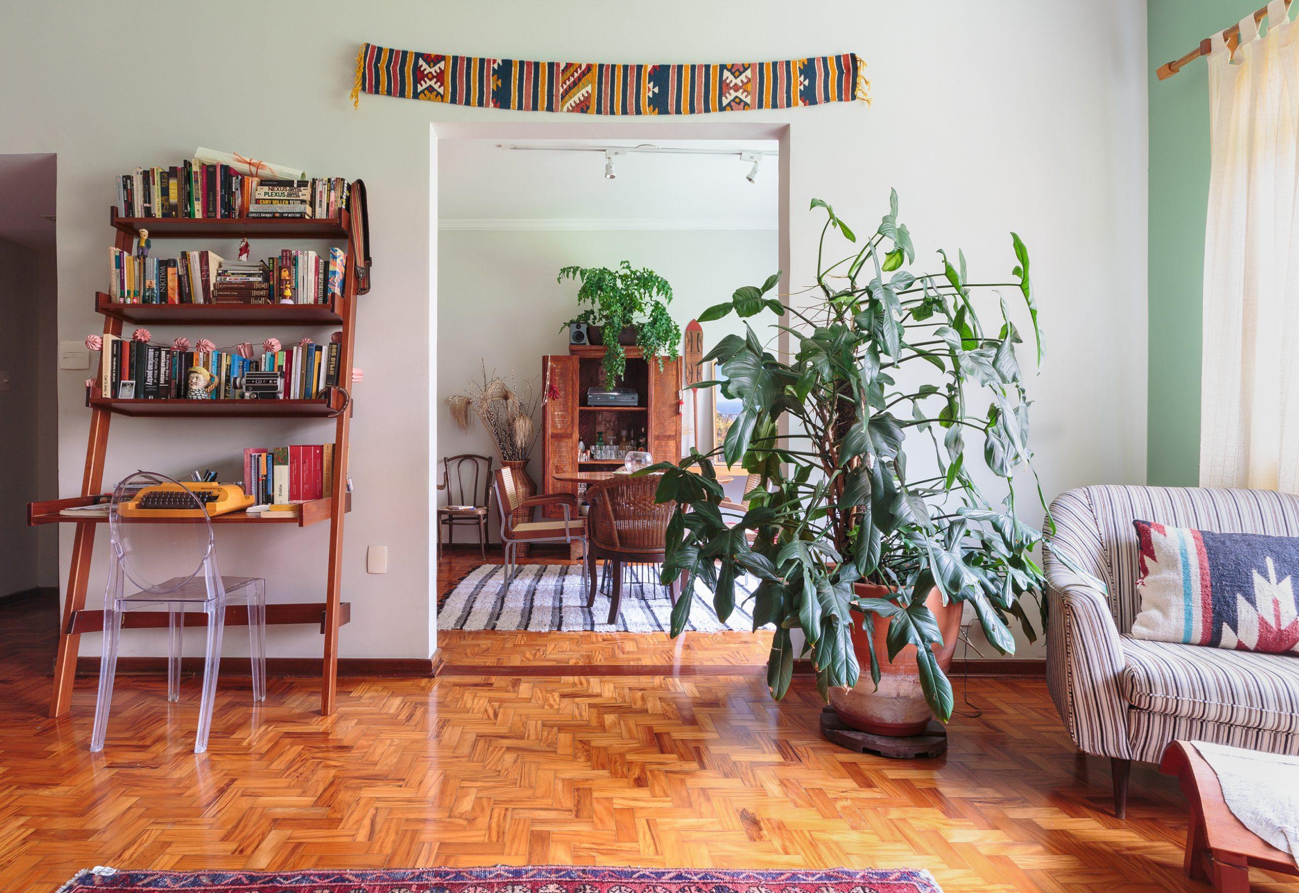 decoração sala com plantas, cadeira ghost e estante de madeira