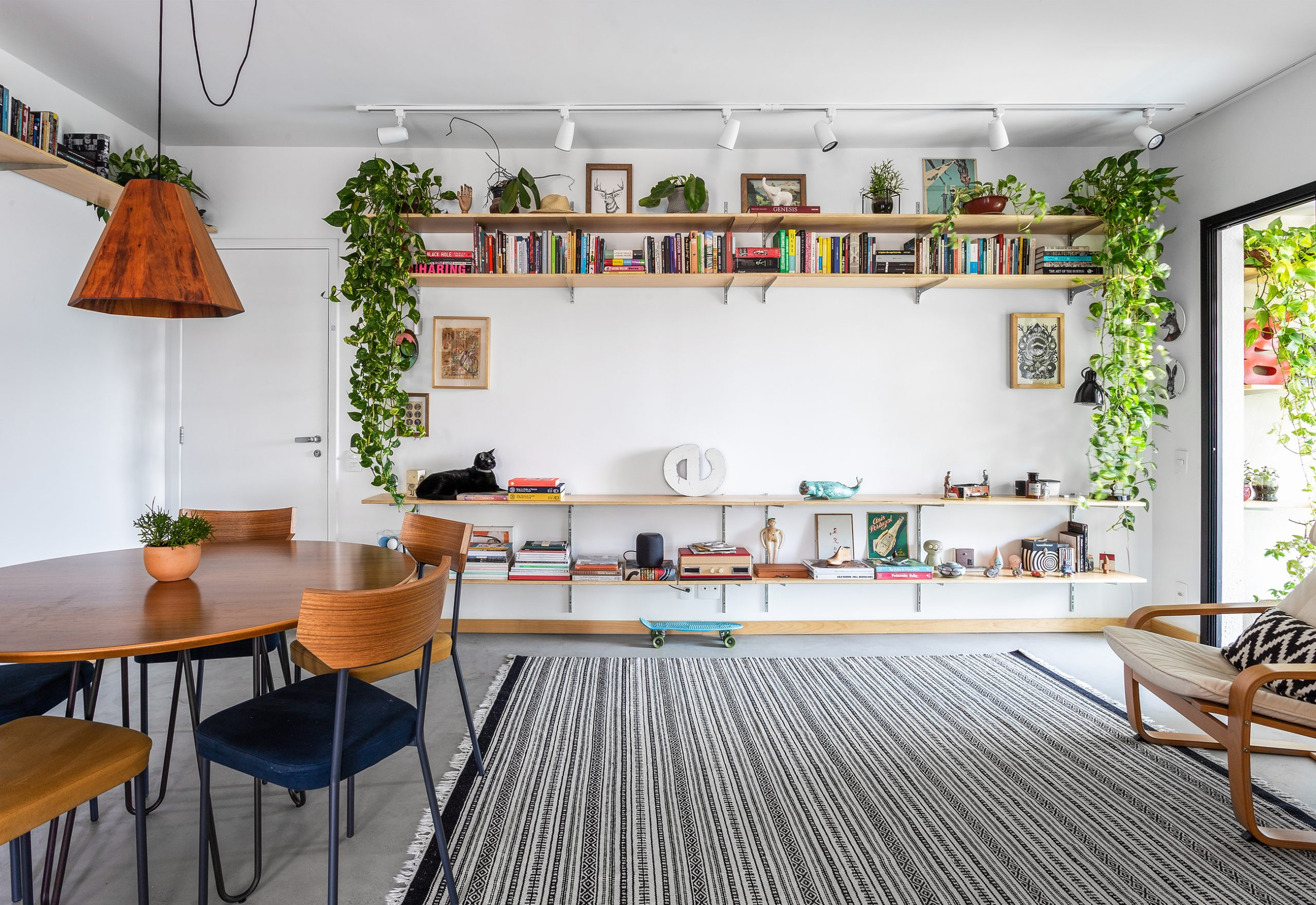 decoração sala com prateleiras e mesa de madeira com plantas