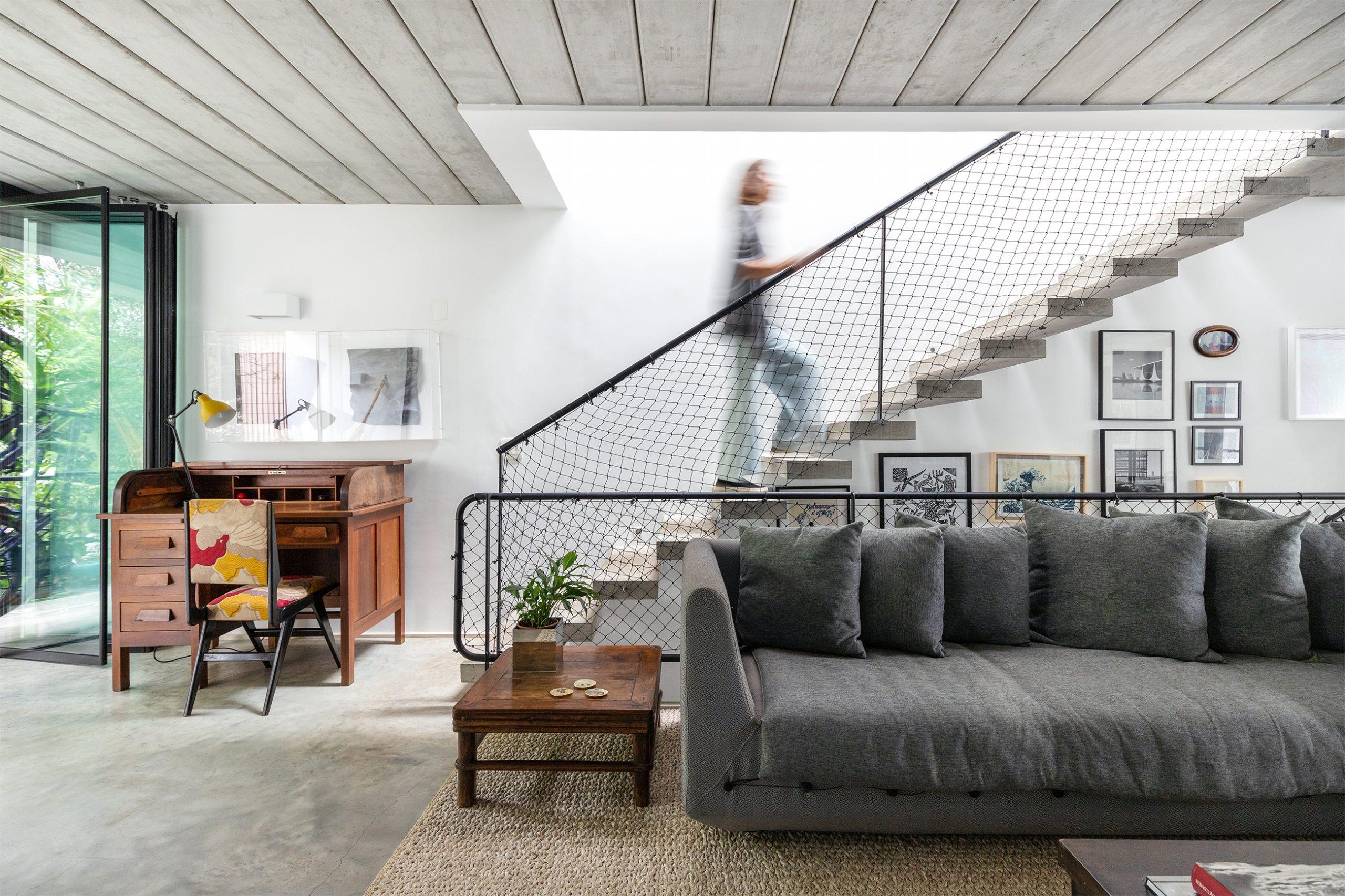 decoração casa sala com sofá cinza, escrivaninha de madeira e escada de concreto