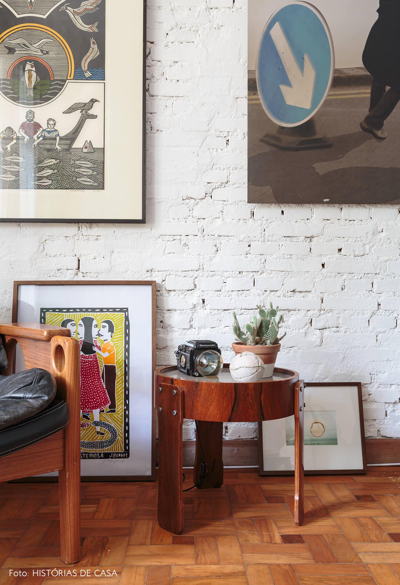 decoração sala com parede de tijolos brancos com muitos quadros