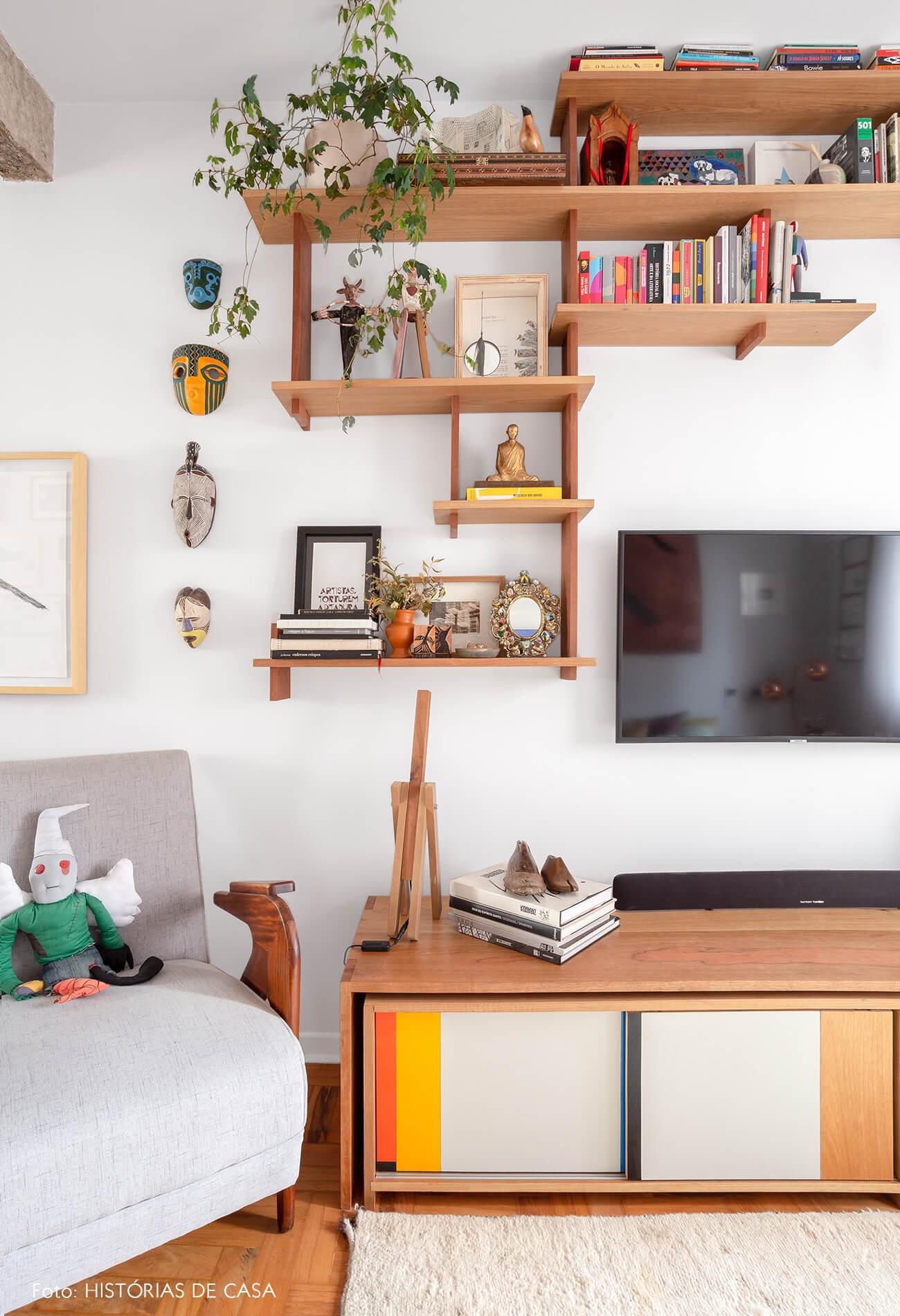 decoração sala com prateleira de madiera e poltrona cinza
