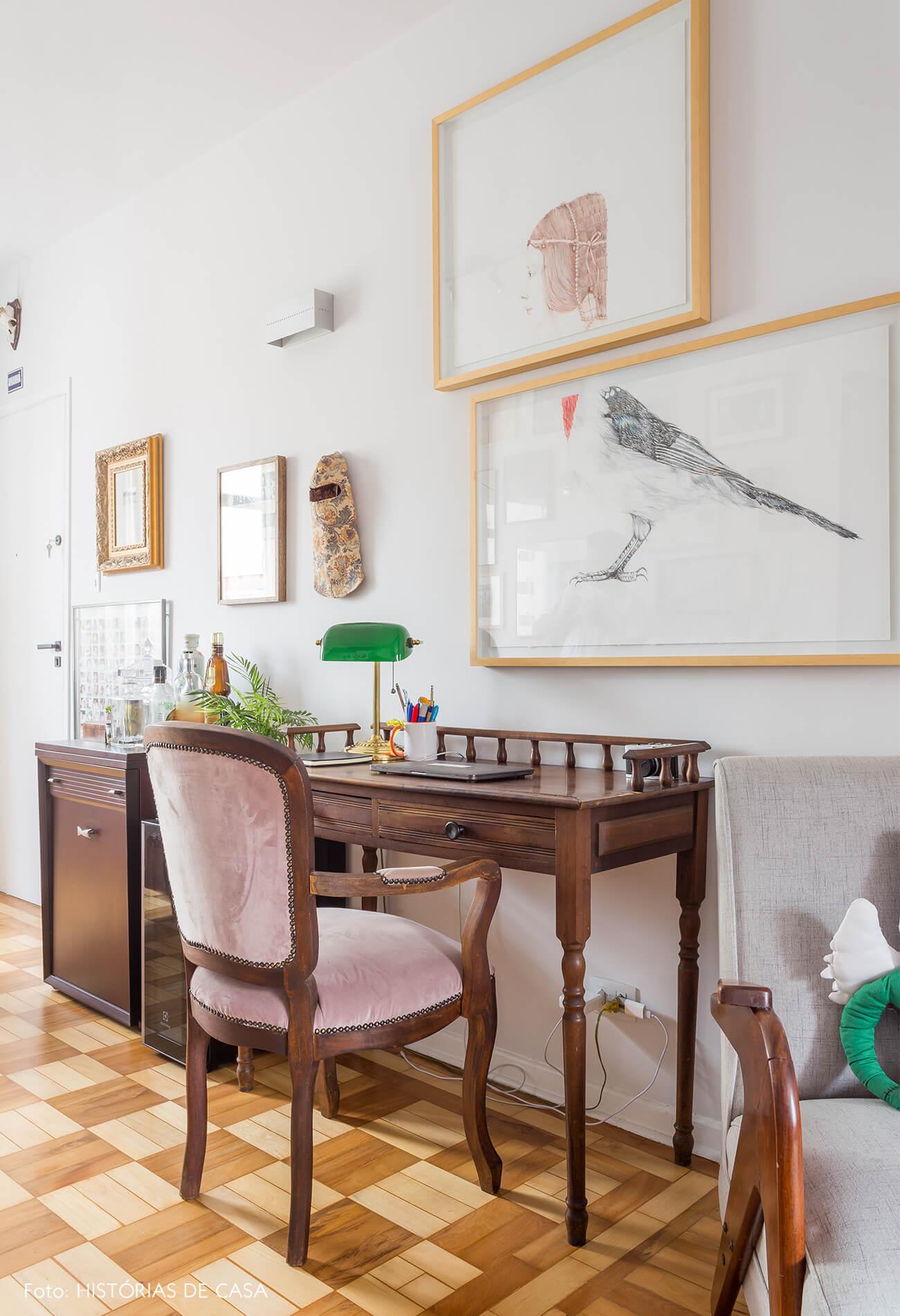 decoração sala com escrivaninha e cadeira de madeira vintage e muitos quadros