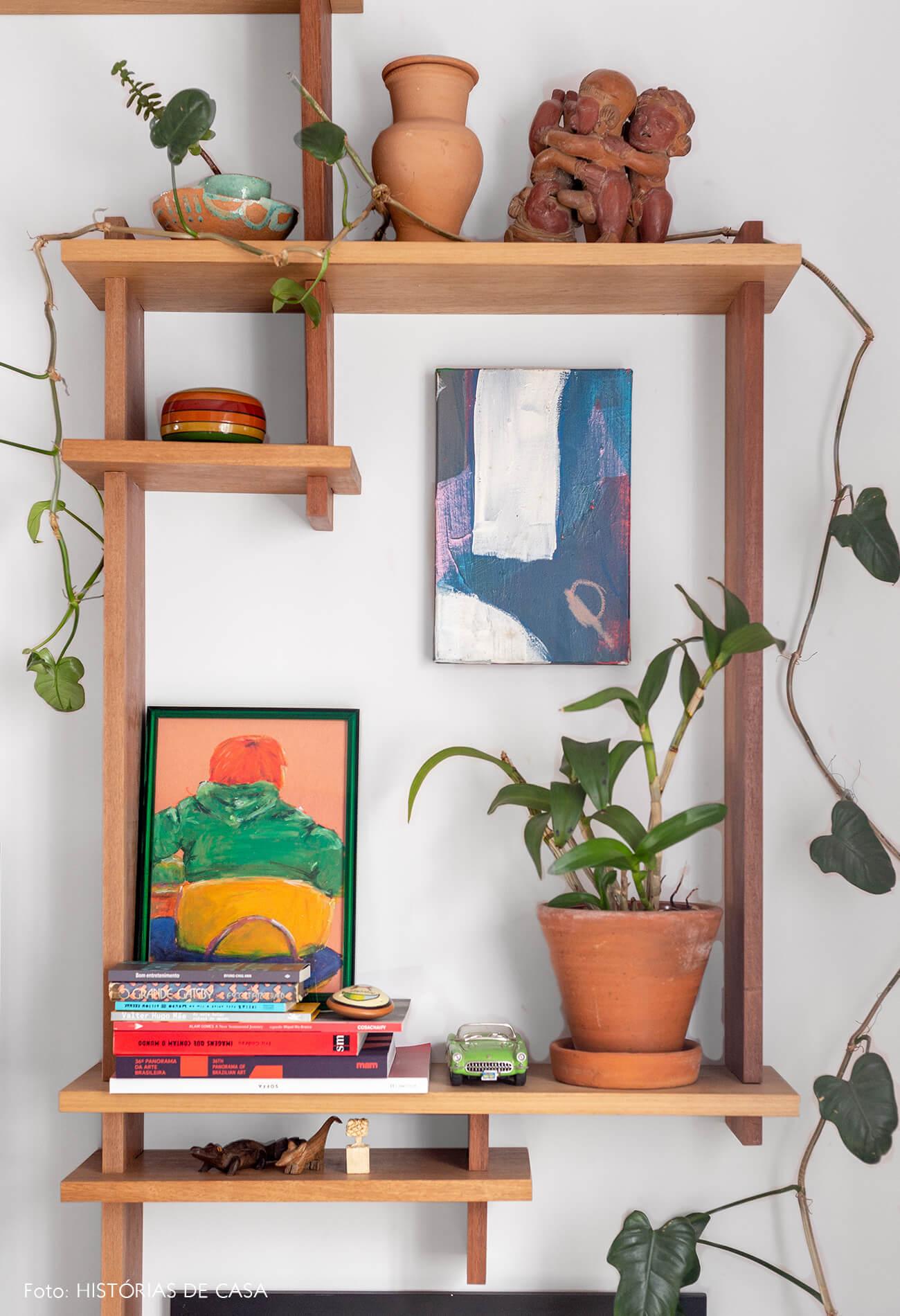 decoração sala com prateleira de madeira e varios quadros