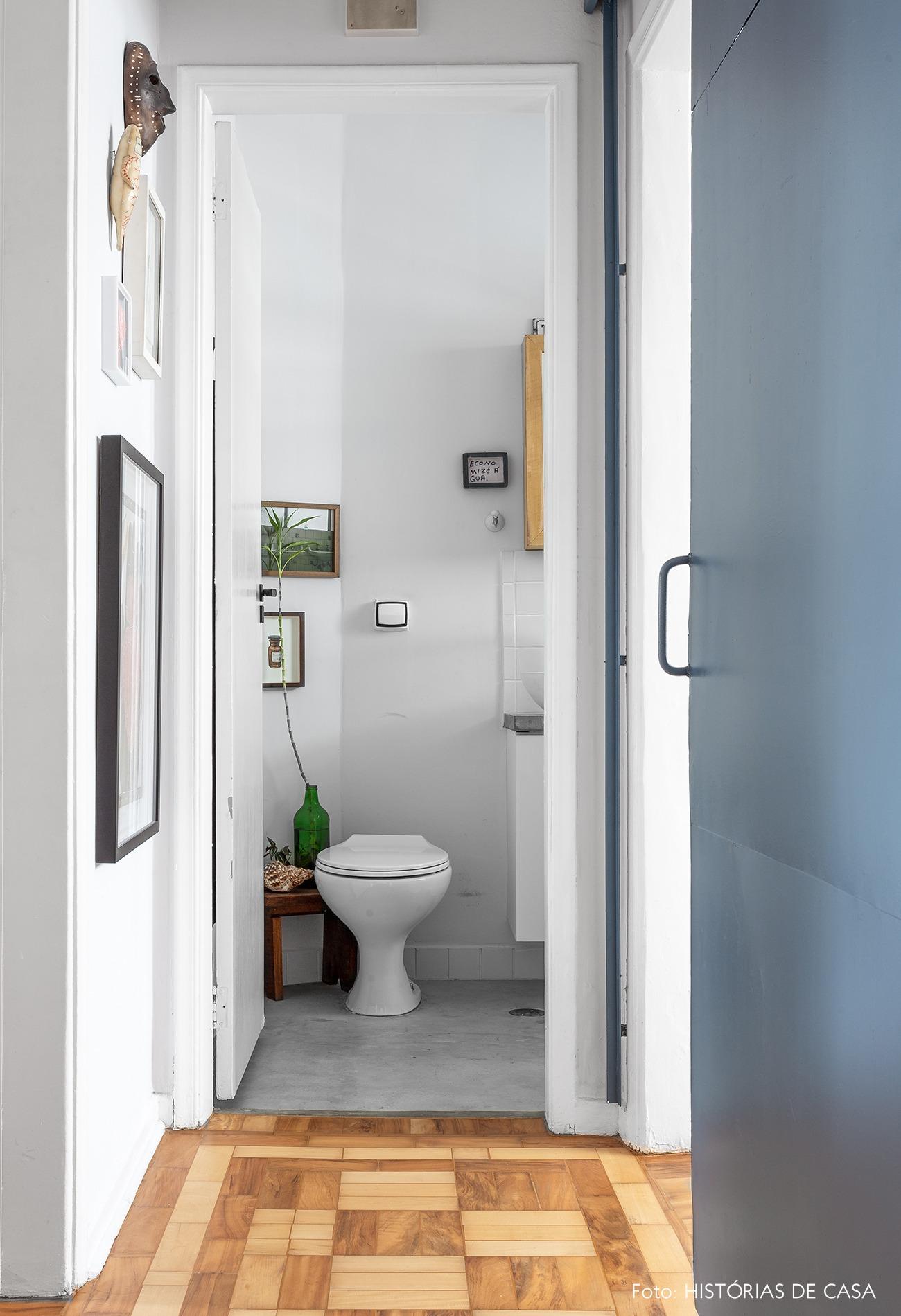 decoração corredor com piso de taco de madeira e banheiro com plantas