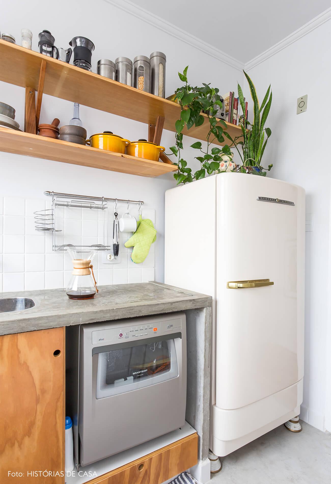 decoração cozinha com armarios de madeira, piso de cimento queimado, e geladeira vintage