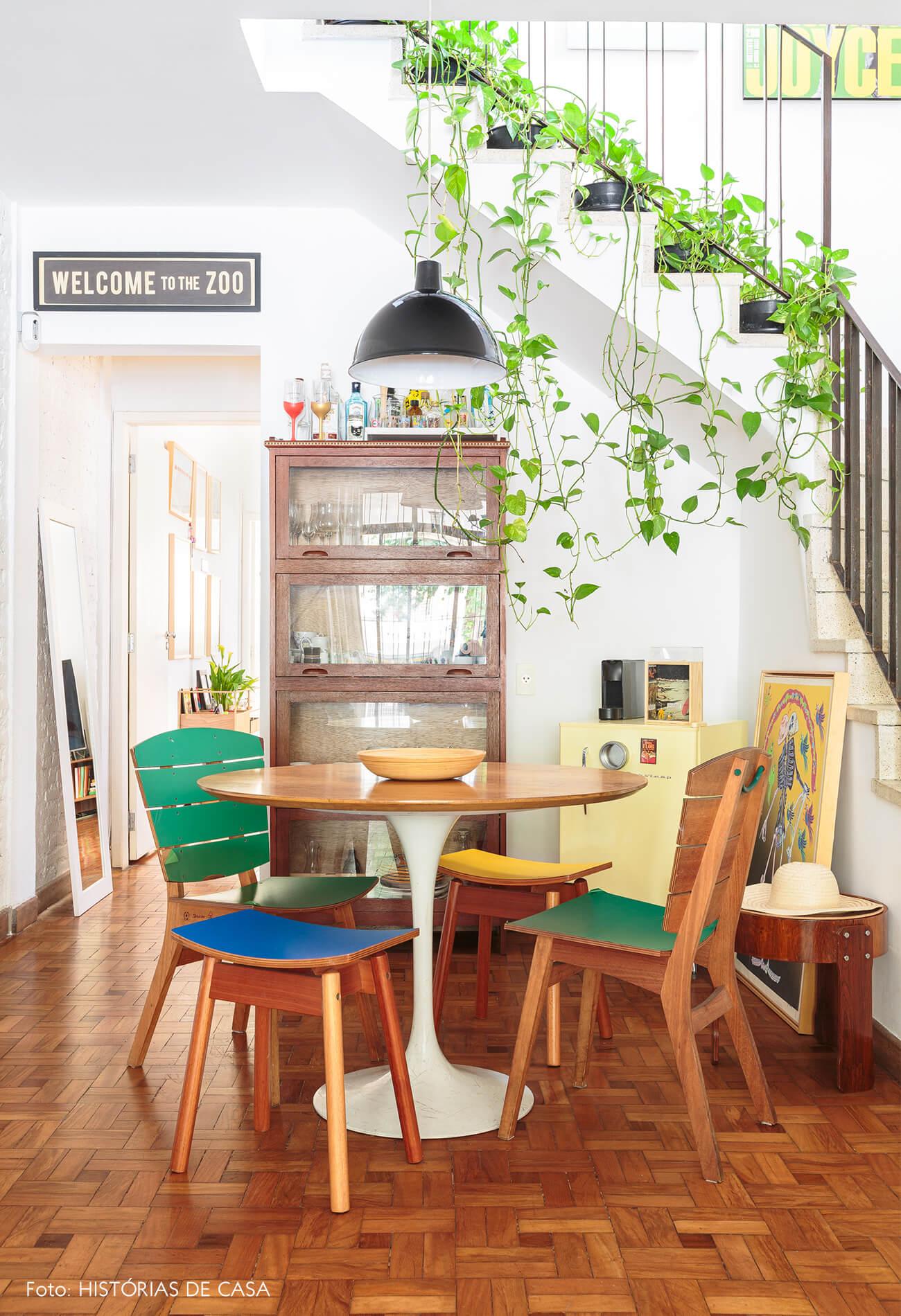 decoração sala jantar com mesa de madeira e cadeiras coloridas