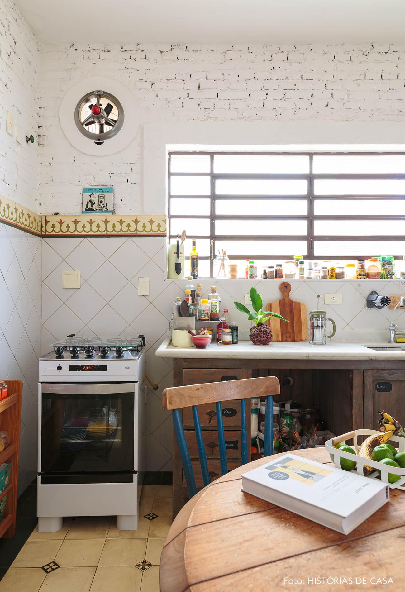 decoração cozinha com parede de tijolos brancos e azulejos coloridos mesa de madeira