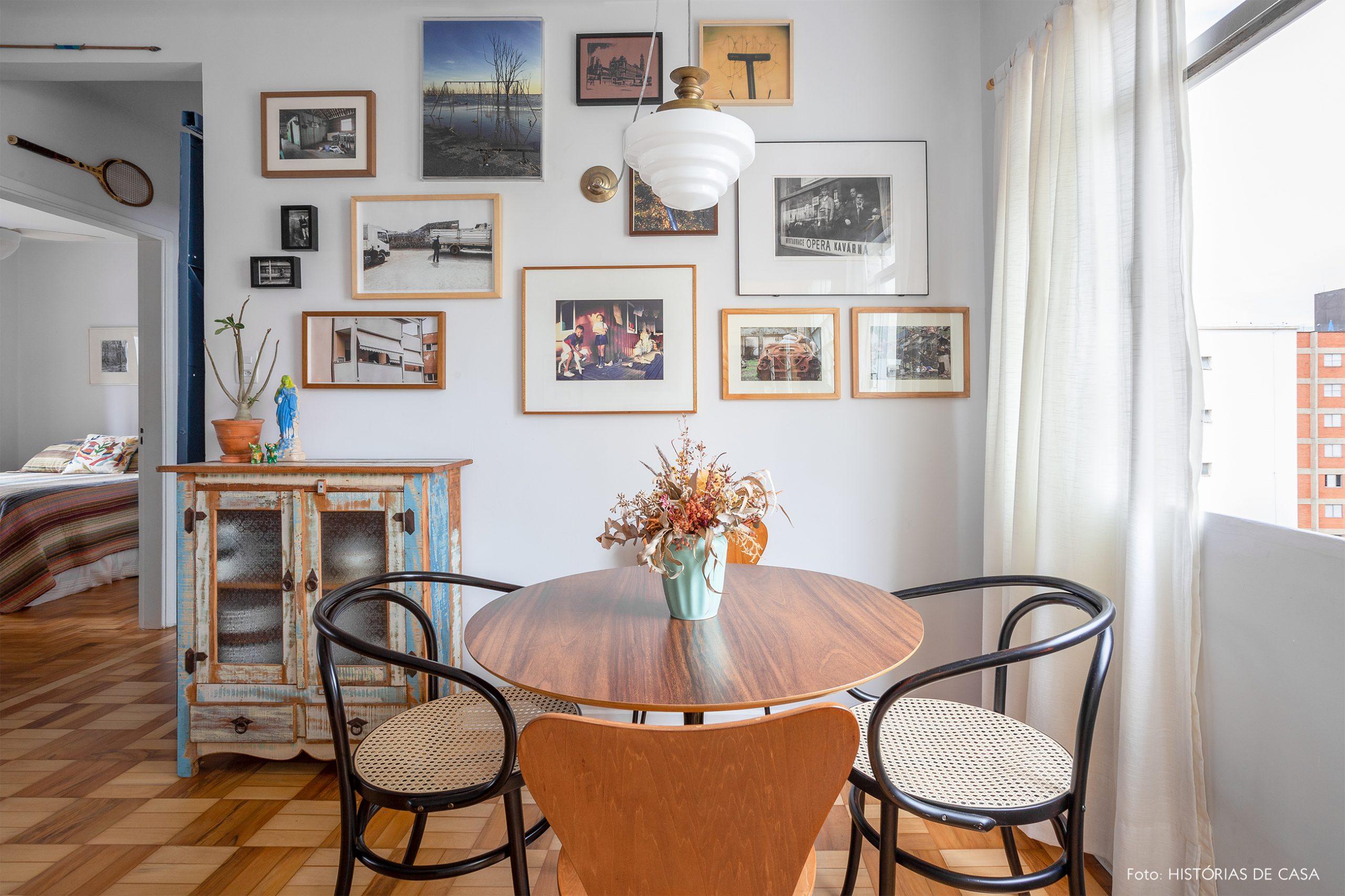 decoração sala jantar com mesa redonda de madeira e muitos quadros