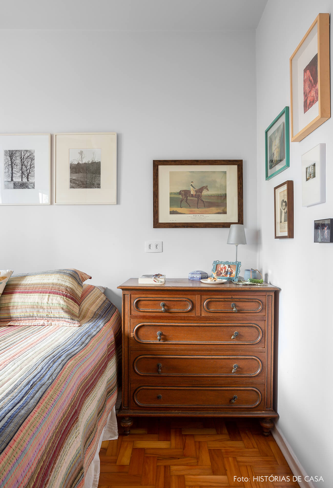 decoração quarto com muitos quadros e armario de madeira