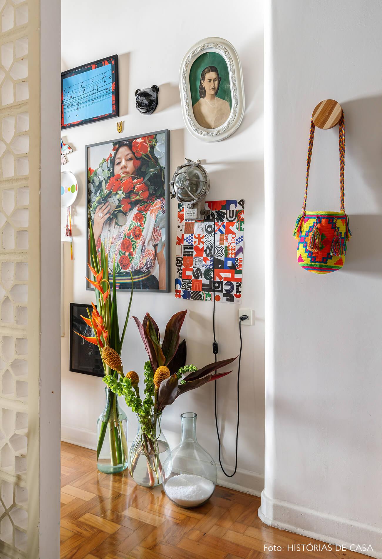 decoração hall entrada com parede de cobogos e muitos quadros
