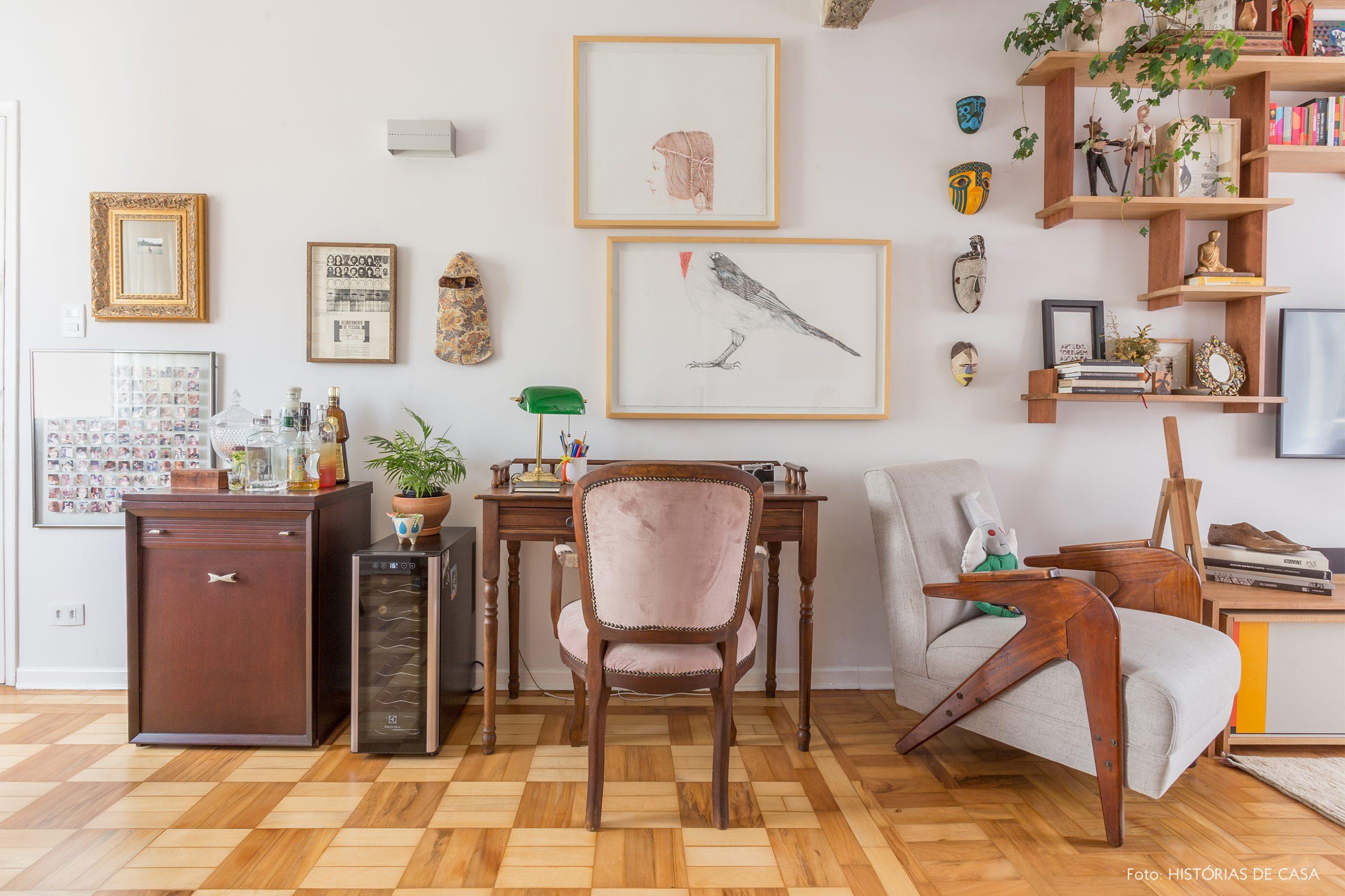 decoração sala com escrivaninha e cadeira antiga de madeira e muitos quadros