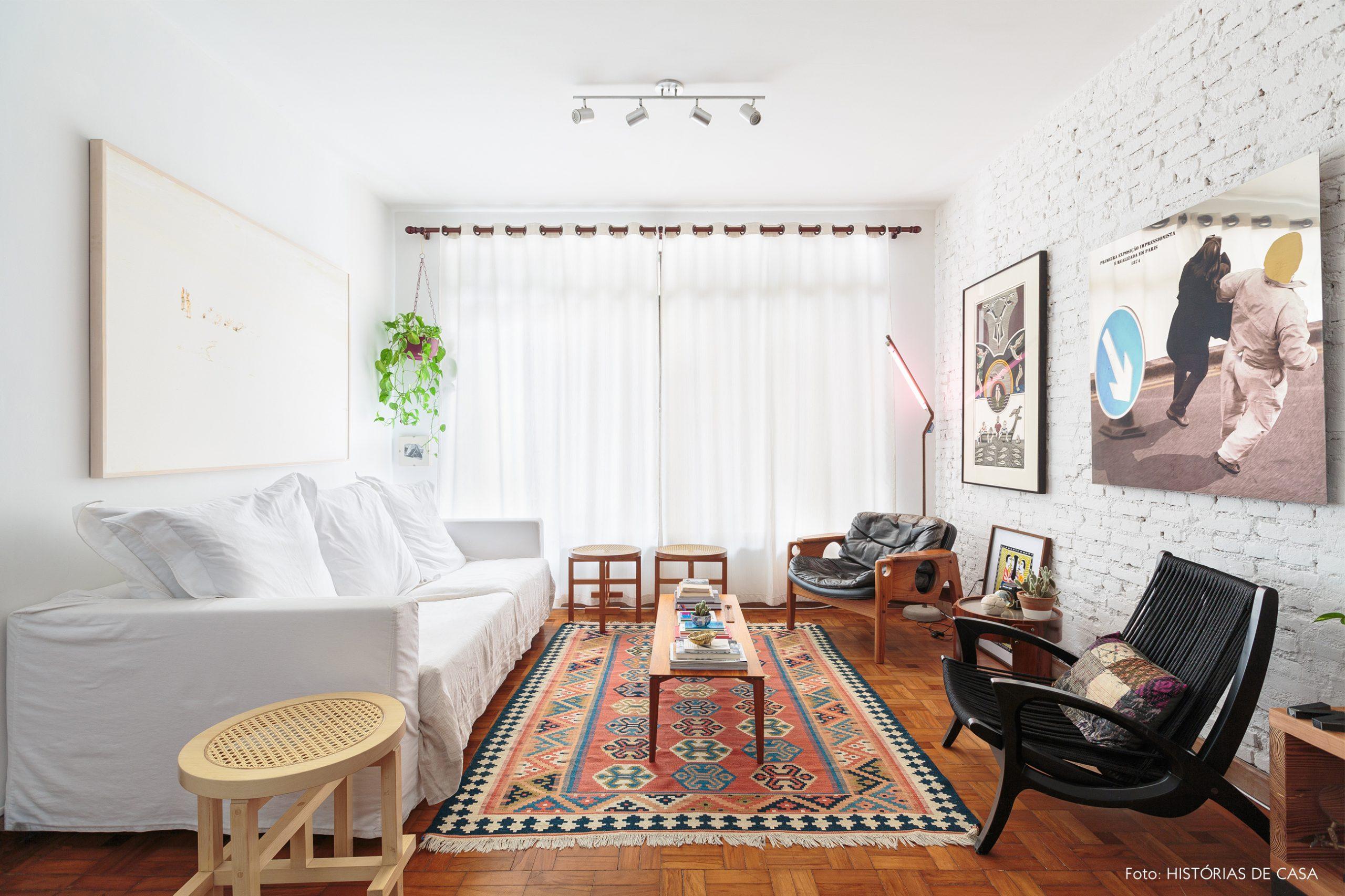 decoração sala com sofa e parede de tijolos brancos e quadros