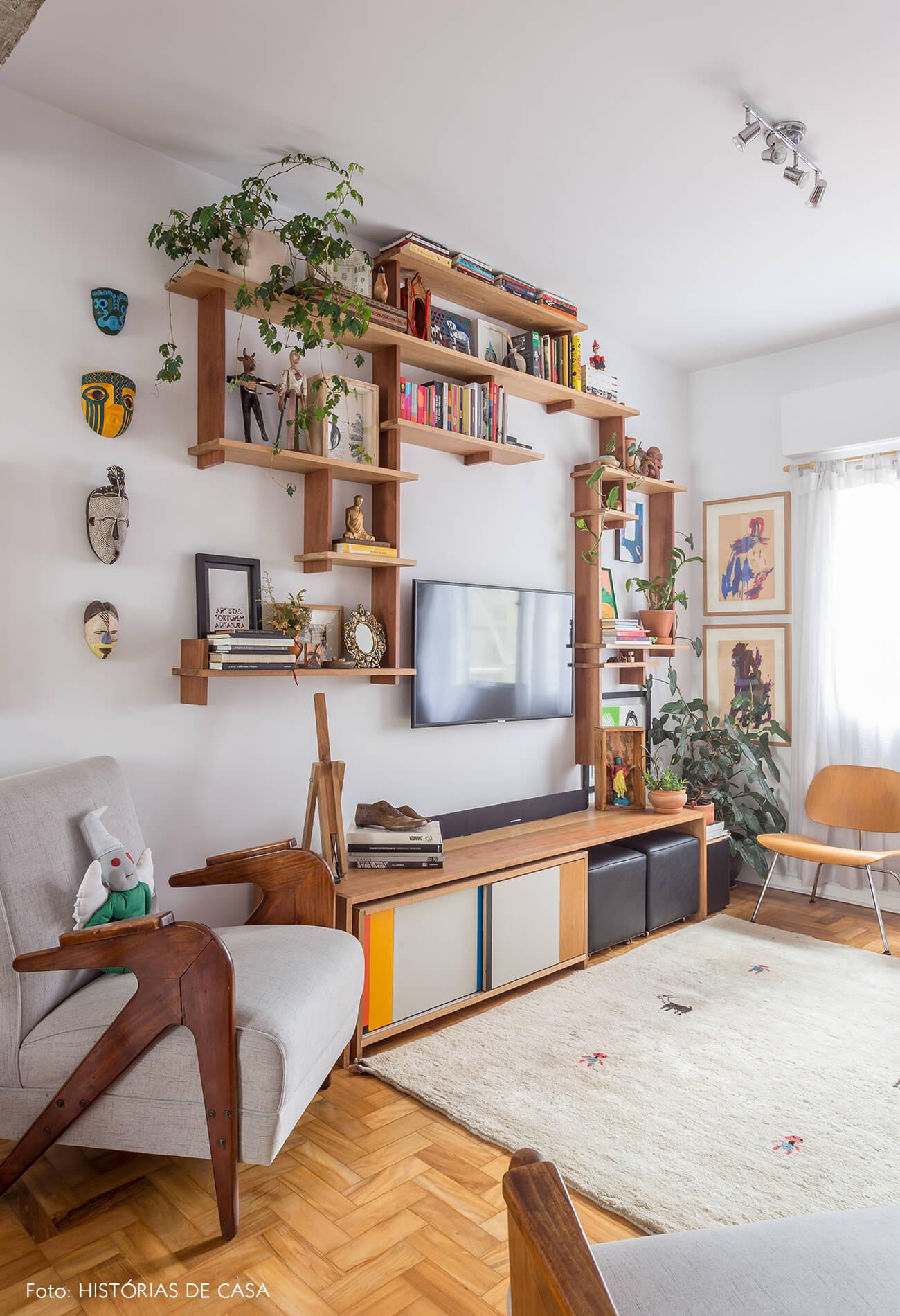 decoração sala com prateleira e rack de madeira e poltronas cinzas