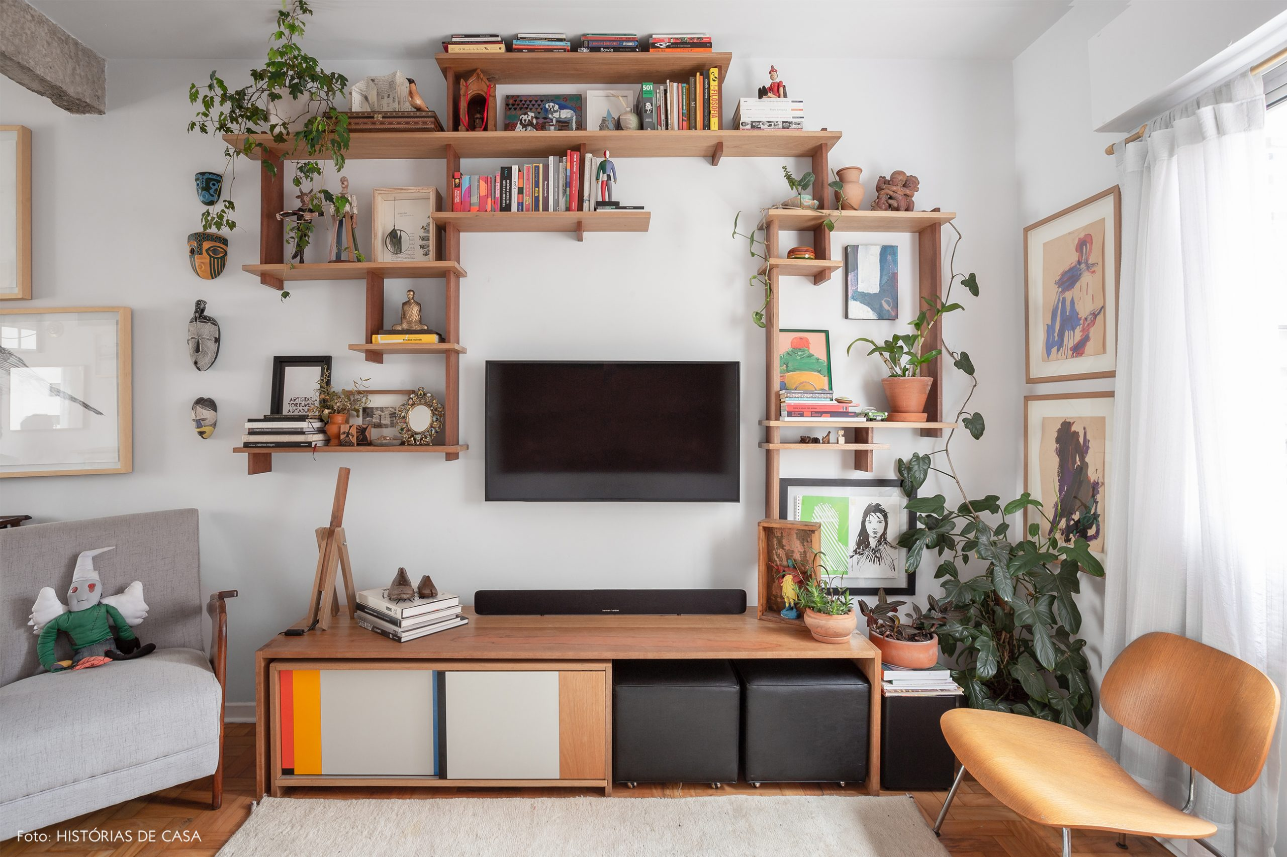 decoração sala com prateleiras de madeira e cadeira eames