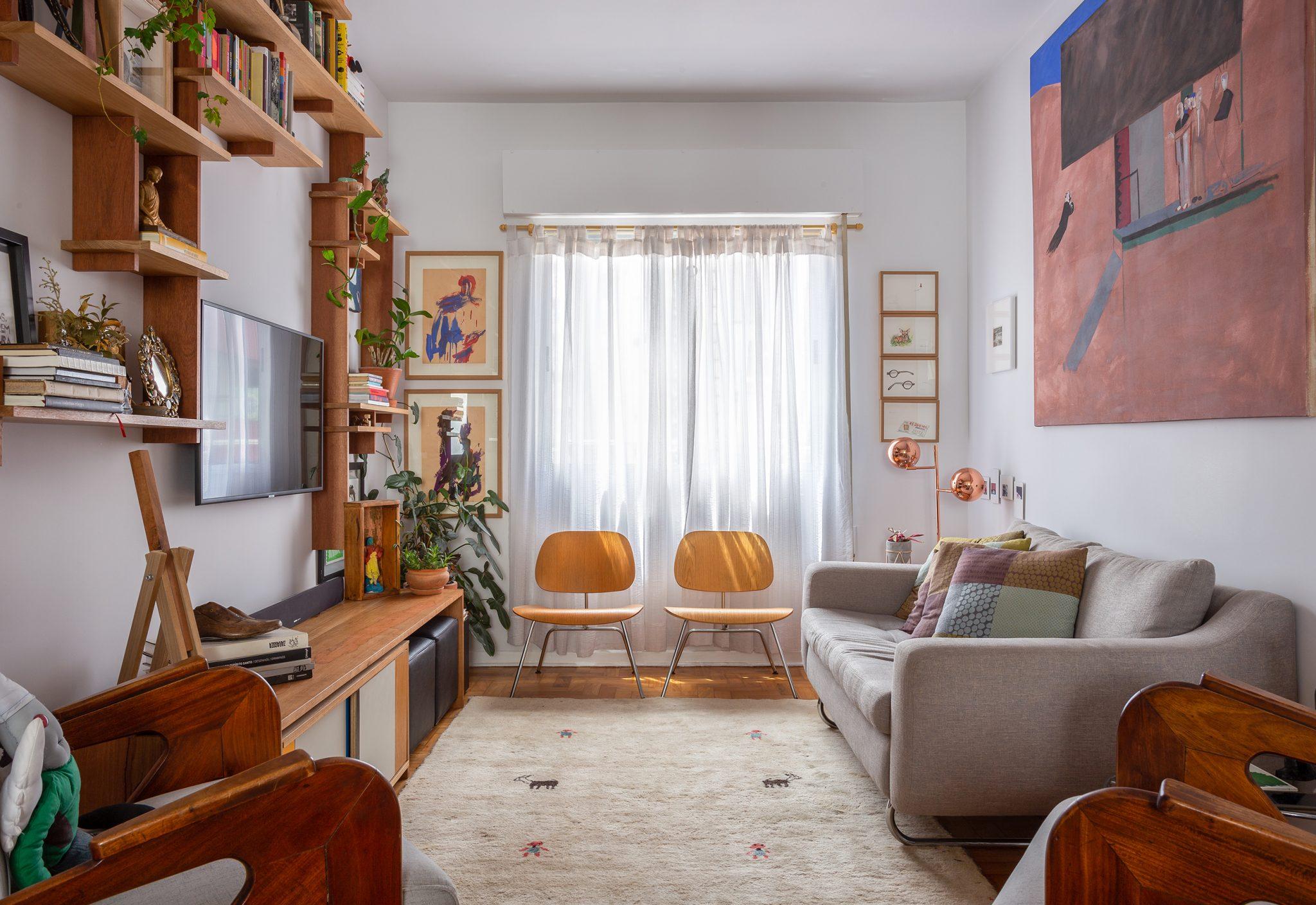 decoração sala com muitos qadros, prateleiras de madeira e cadeira eames