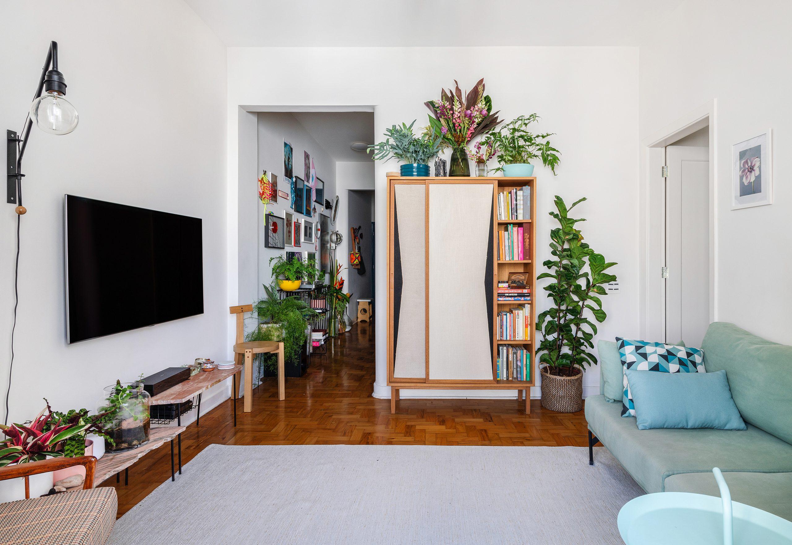 decoração sala com sofa azul muitas plantas banco girafa lina