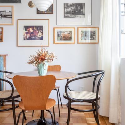 decoração sala jantar com muitos quadros e mesa redonda de madeira