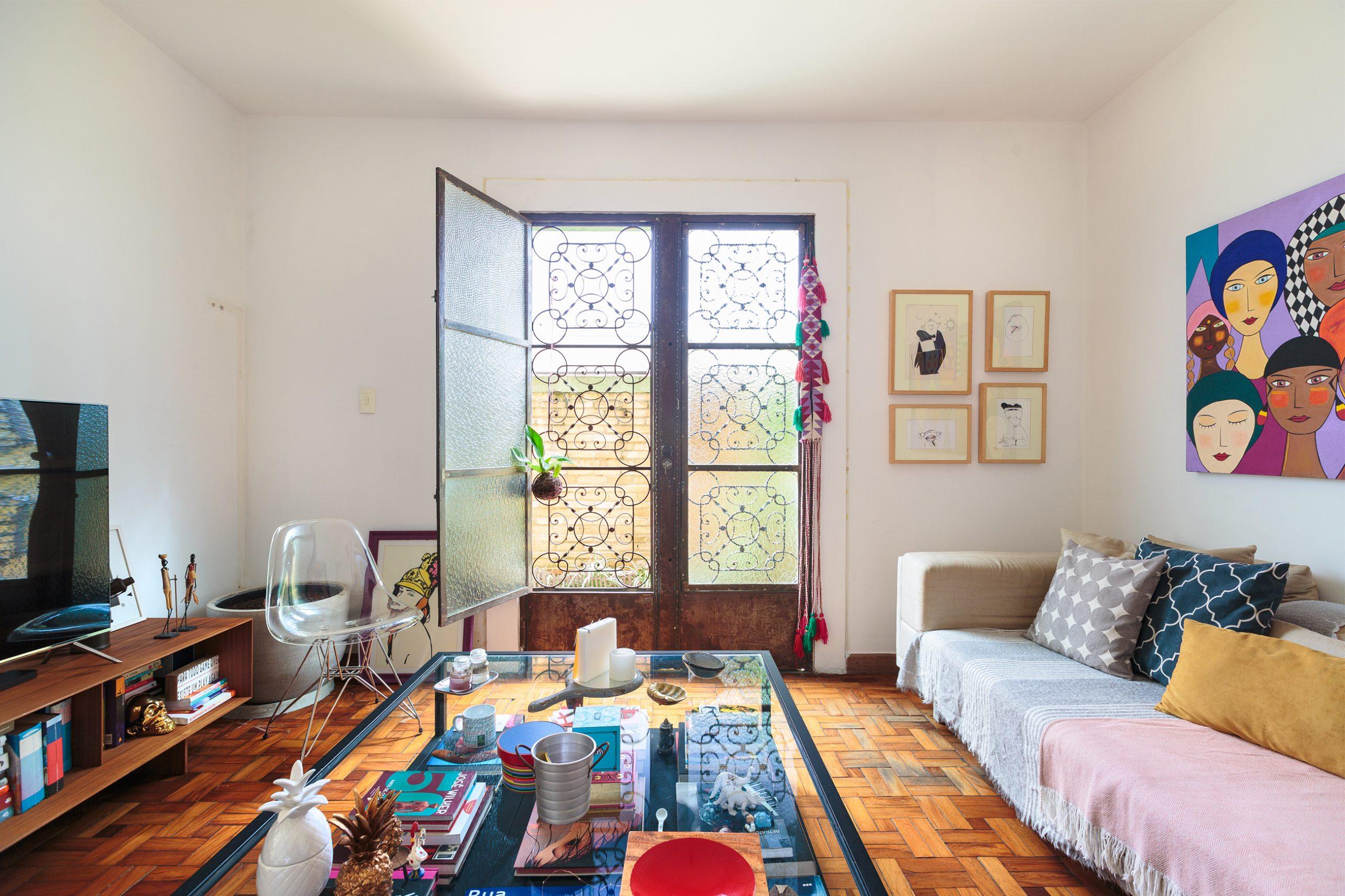 decoração sala colorida com mesa de centro de vidro e quadros
