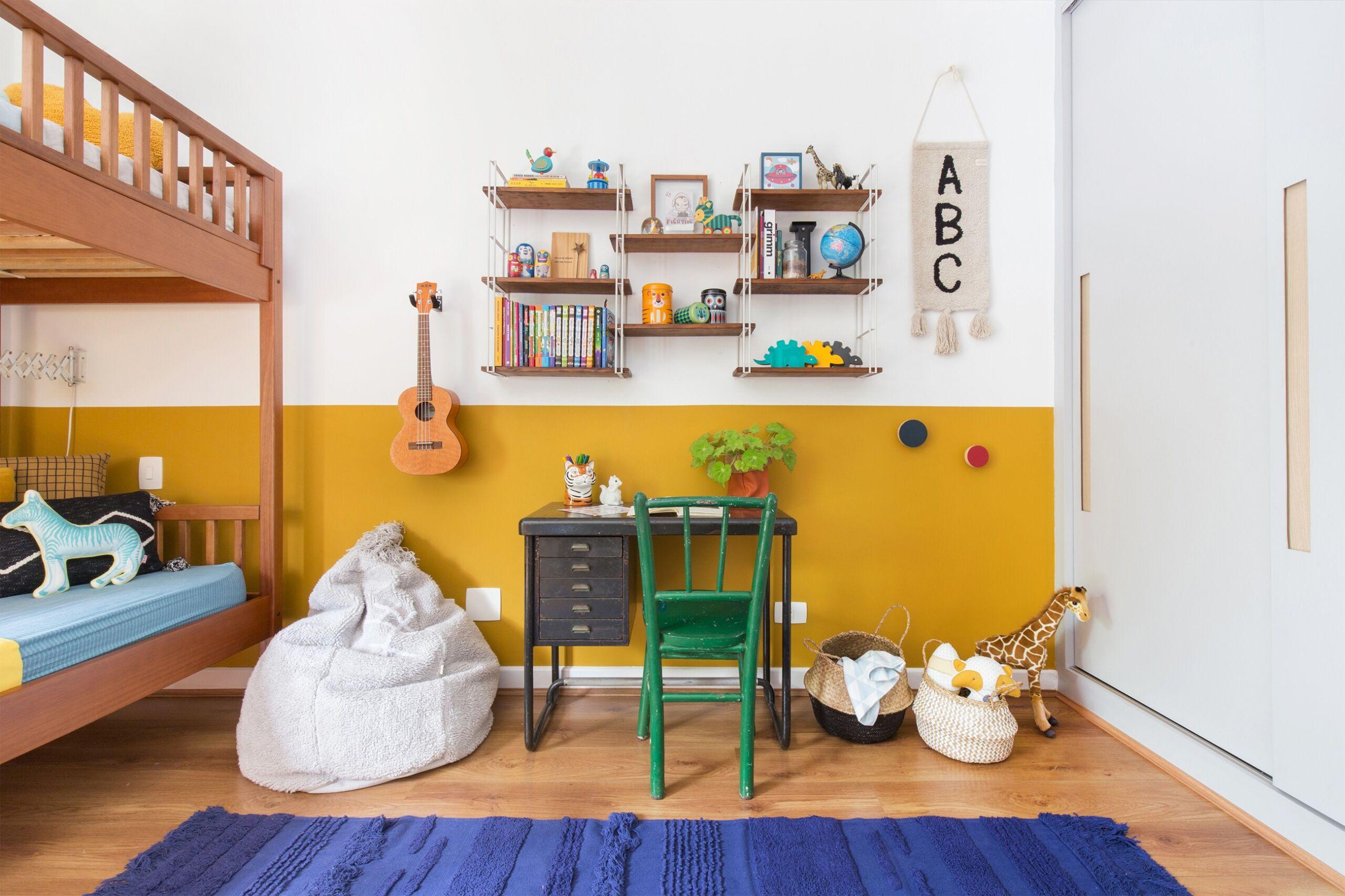 quarto infantil decoração pufe, tapete azul, meia parede amarela