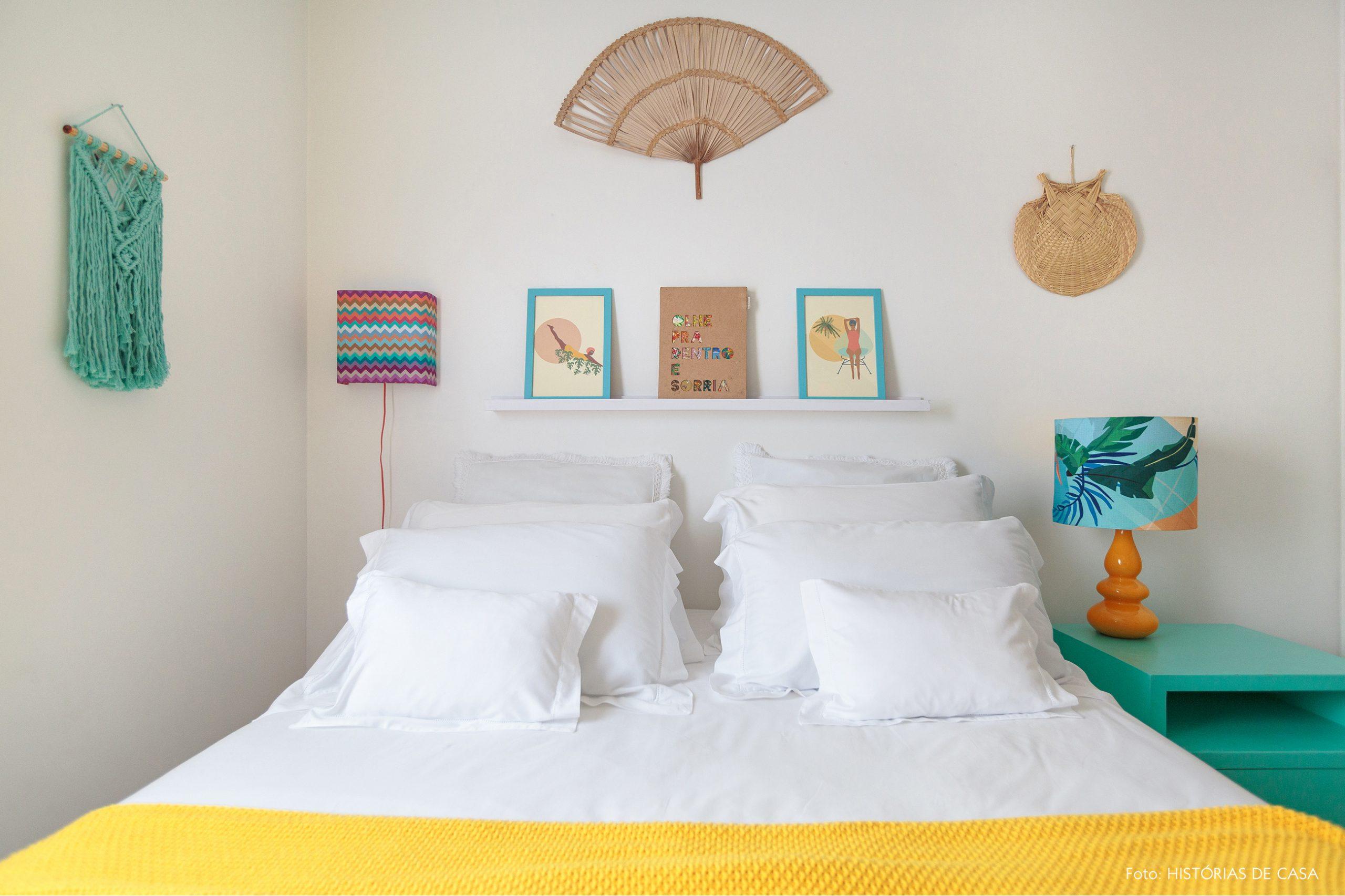 decoração praiana quarto com leques e tapeçaria na parede e luminária colorida