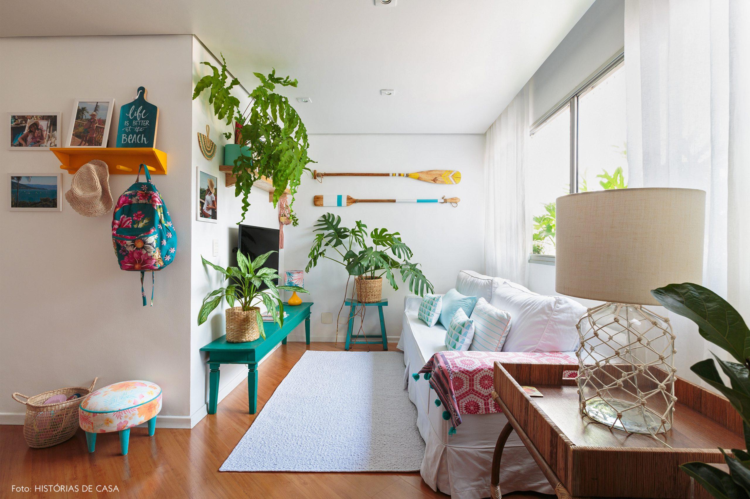 decoração praiana sala com muitas plantas, cestos e bancos azuis de madeira