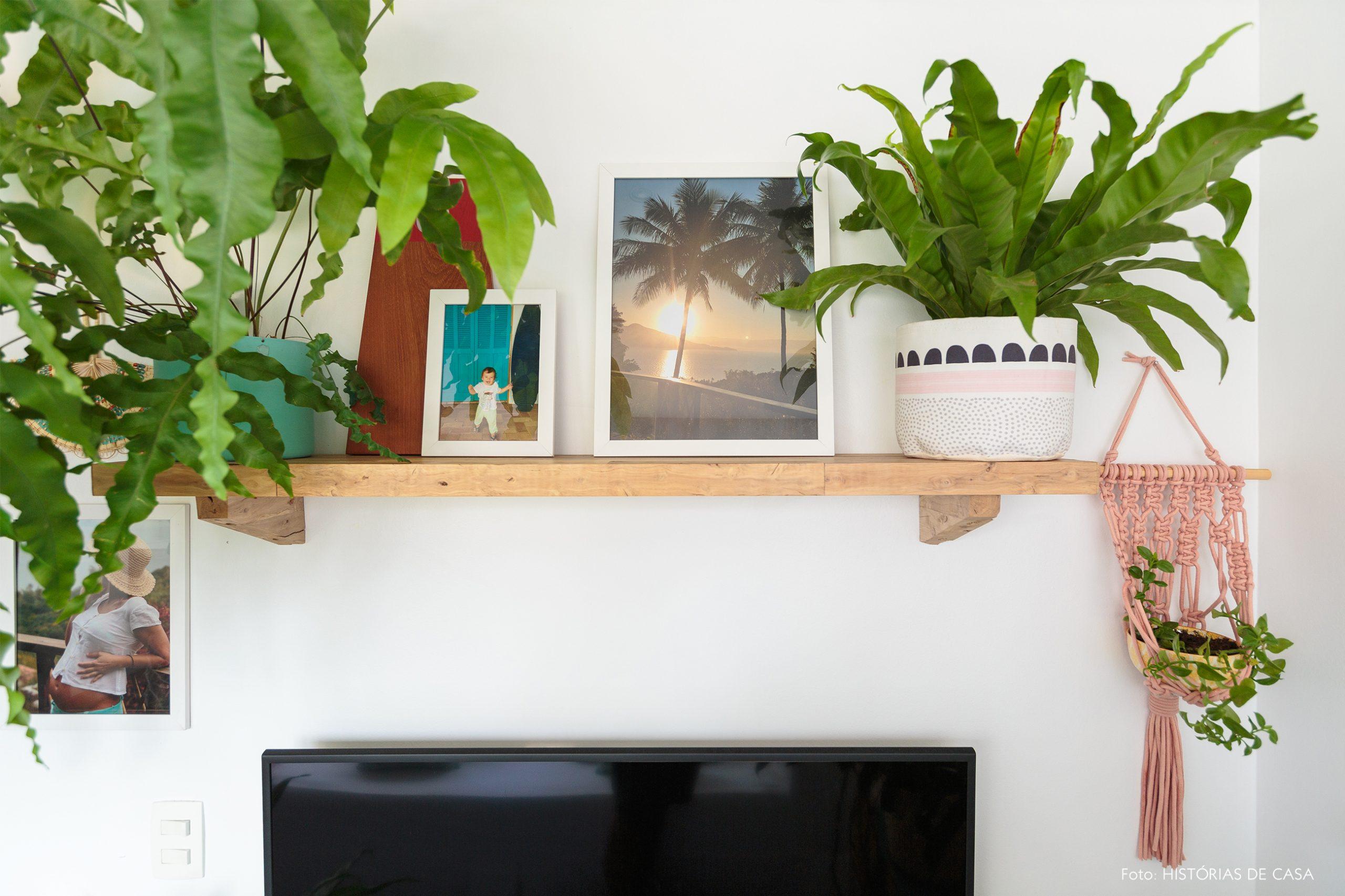 decoração praiana prateleira de madeira na sala com plantas e macrame