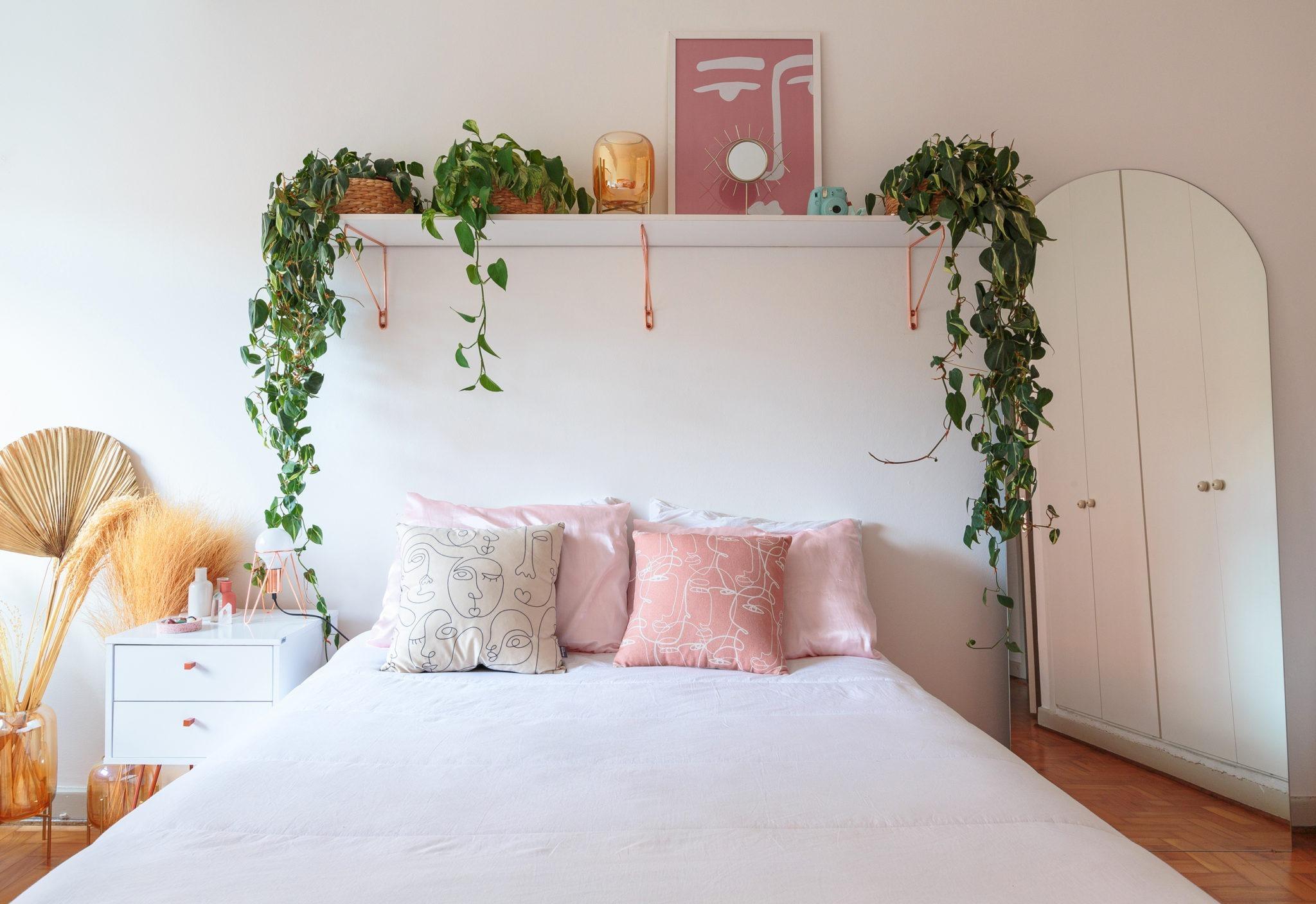 Quarto com prateleira sobre a cama e plantas