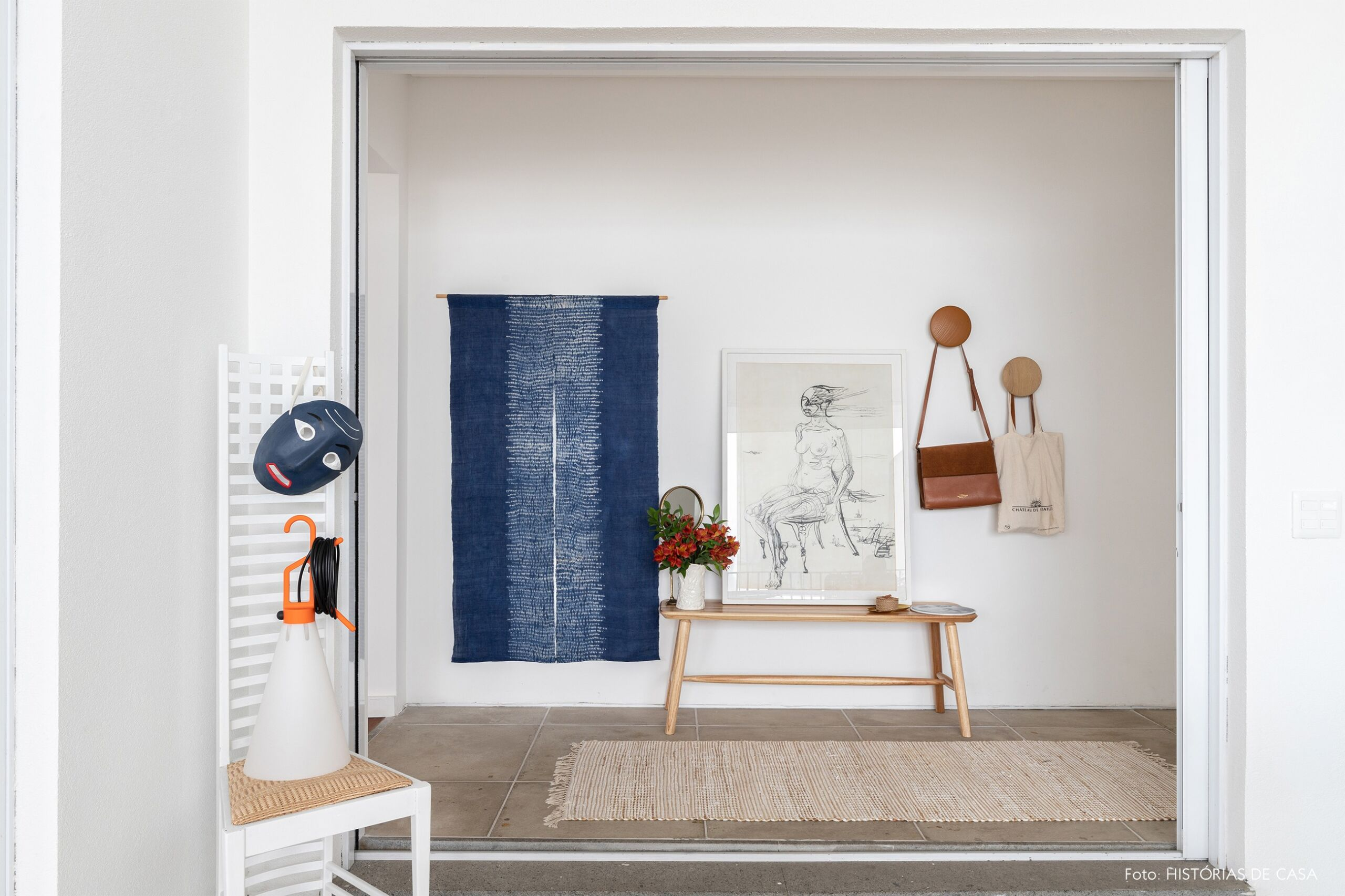decoração hall claro com tecido na parede e ganchos madeira