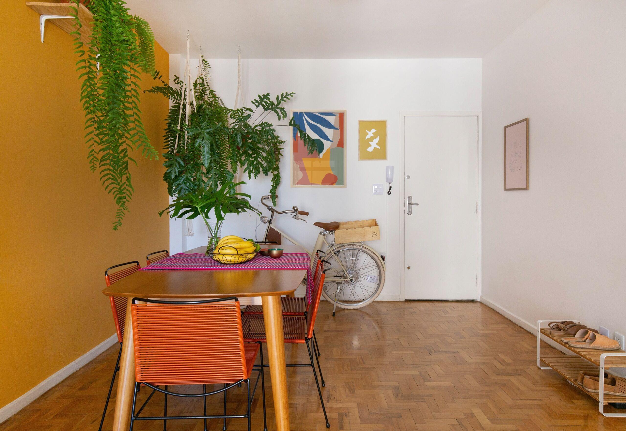 decoração Obrah sala jantar parede mostarda quadros coloridos e muitas plantas
