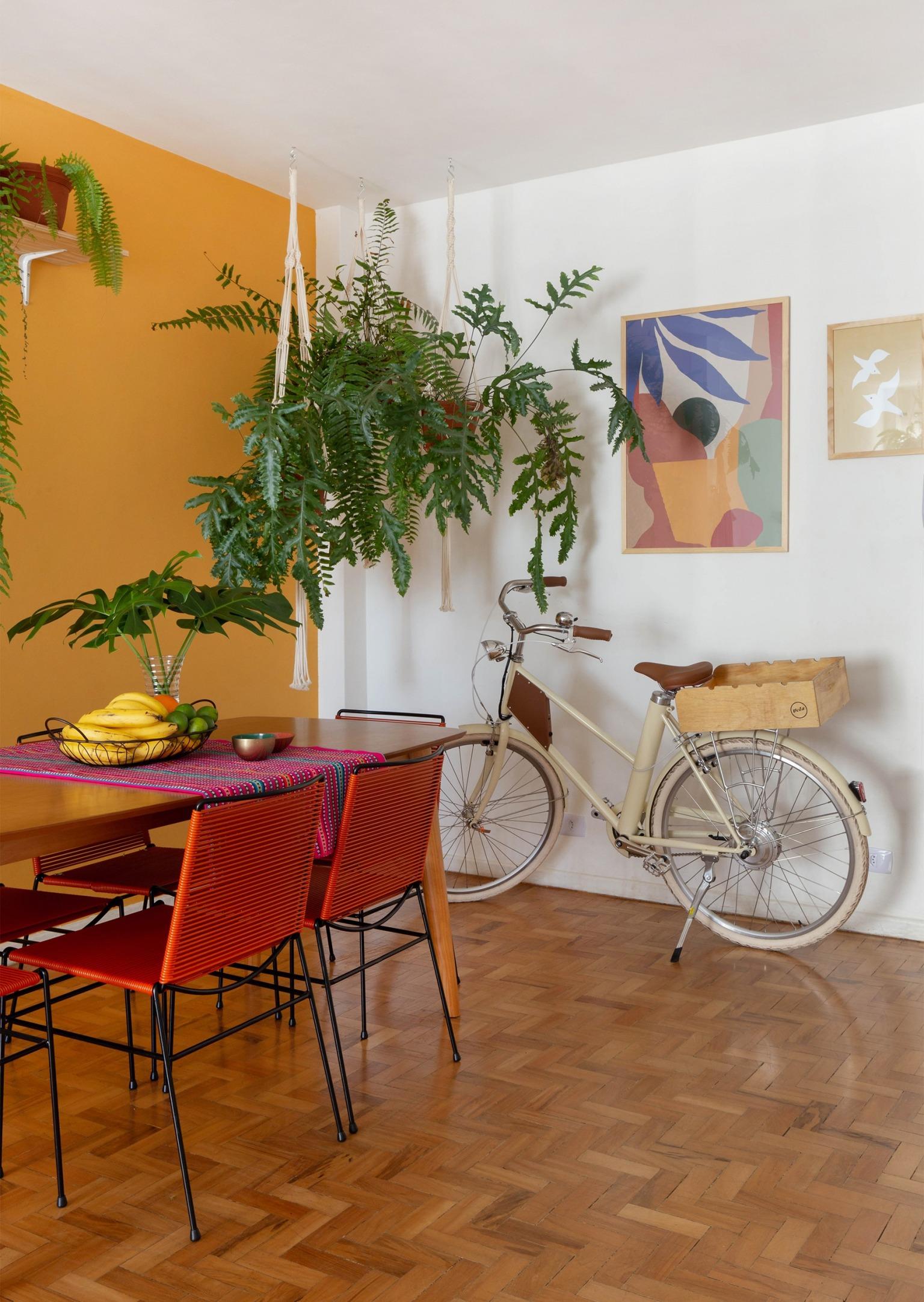 decoração obrah sala jantar parede mostarda quadros coloridos bicicleta e muitas plantas