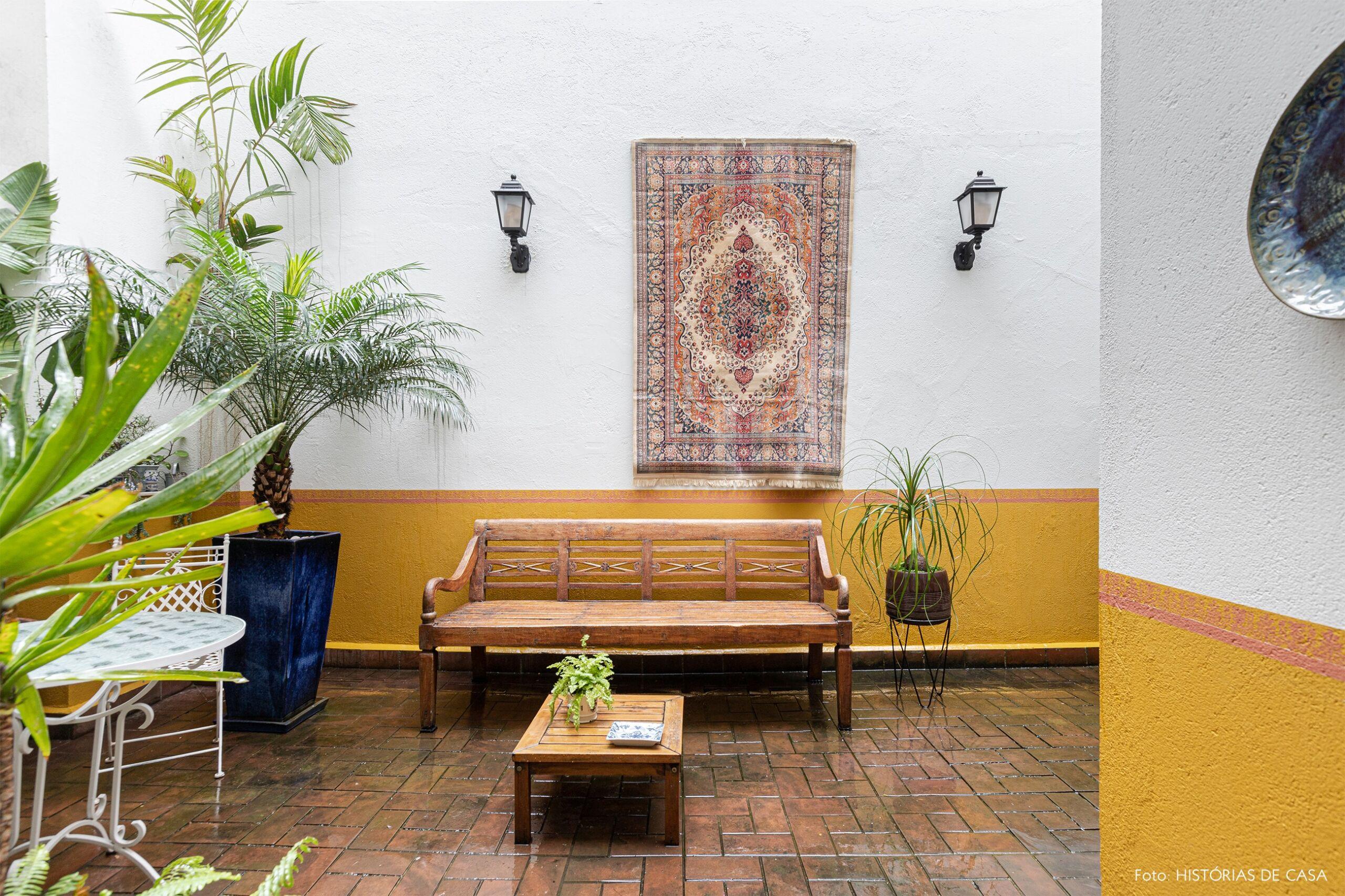 decoração jardim meia parede amarela banco de madeira tapete pendurado em parede