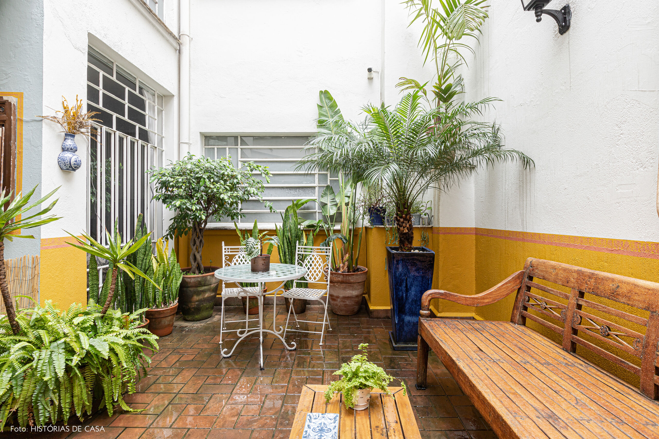 decoração jardim meia parede amarela banco de madeira