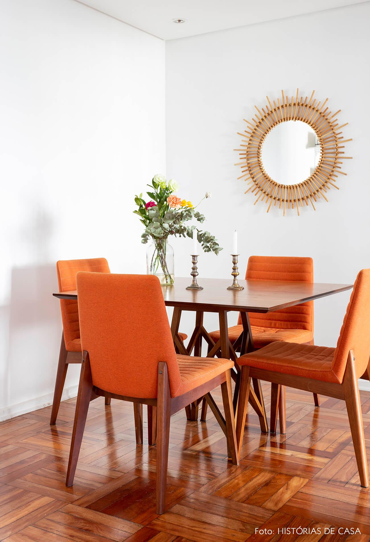 Sala de jantar com cadeiras laranja e piso de tacos