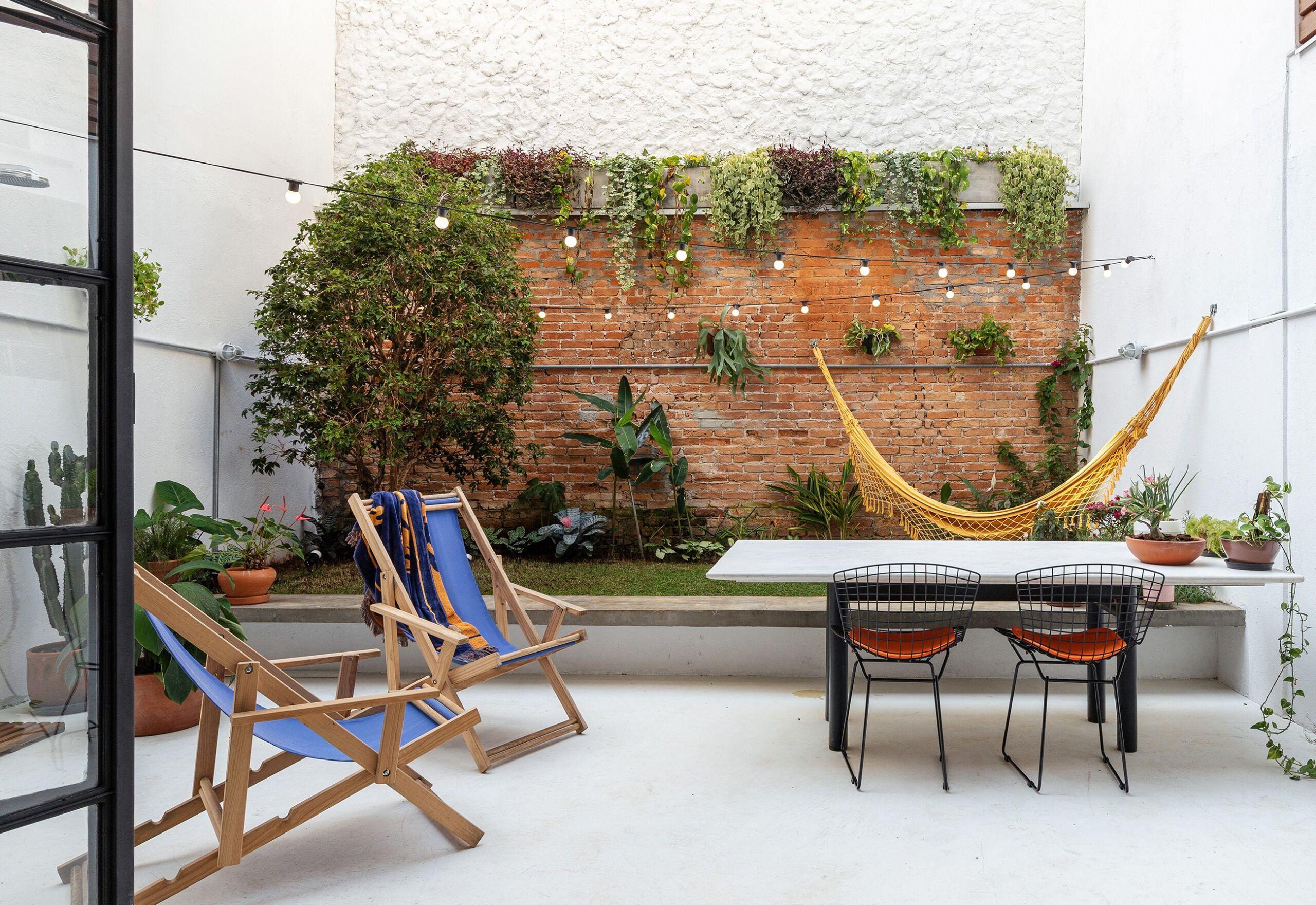 decoração quintal poltronas azuis rede amarela parede tijolos
