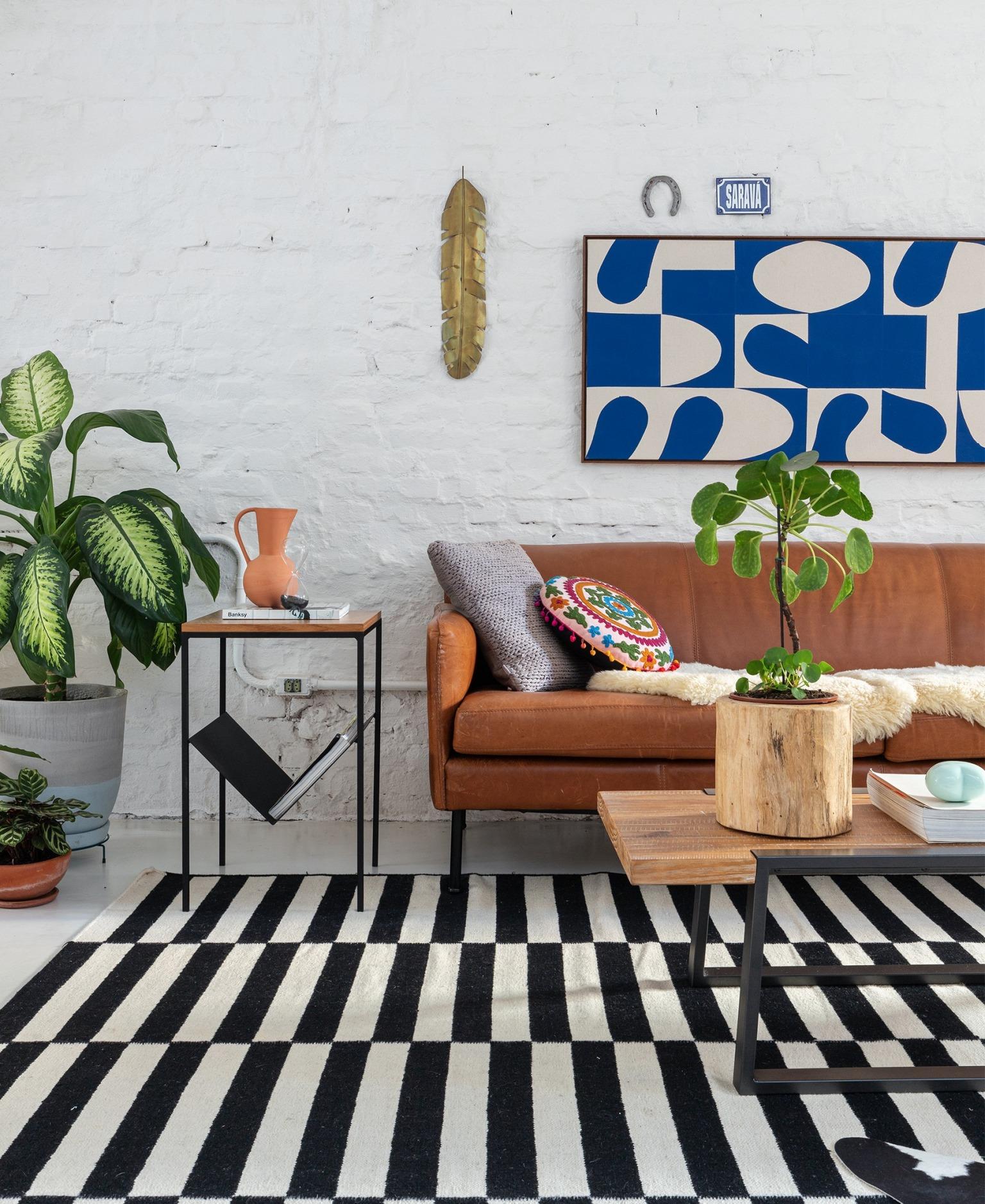decoração sala parede tijolos brancos sofá couro marrom tapete listrado