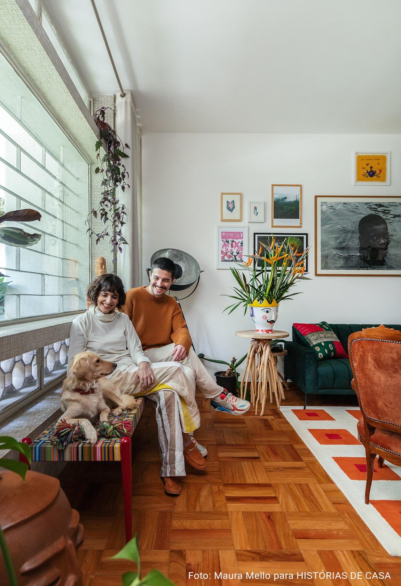 Sala de estar com piso de tacos e parede de quadros